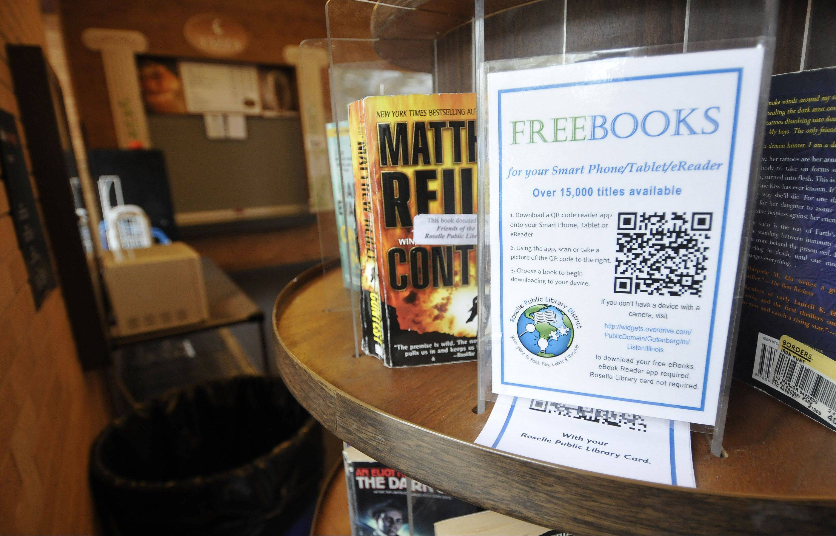 The Roselle Public Library is now providing a QR code that allows any user to access thousands of free e-books at its Friends of the Library kiosk. The kiosk is also full of paperbacks which can be borrowed on the honor system. The sign says leave a paperback book and take another one to read from the rotary shelves.