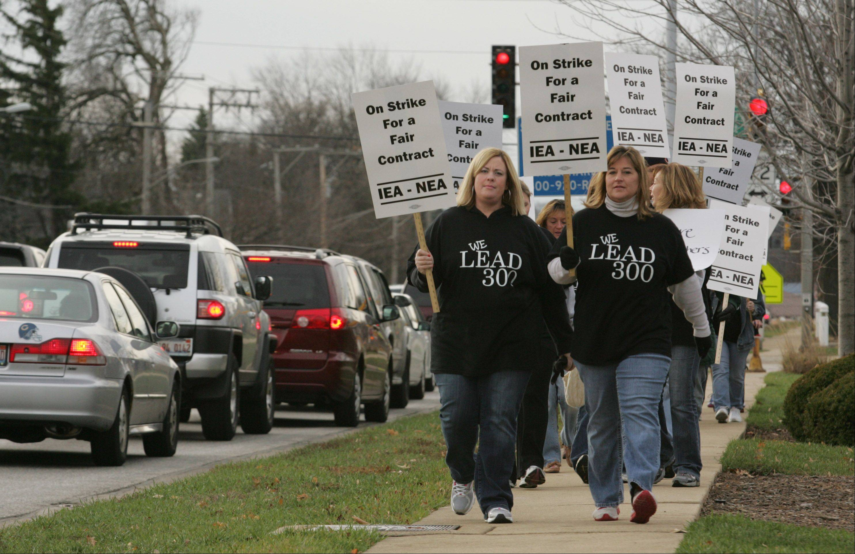 Community Unit District 300 teachers walk along Route 31 in West Dundee Tuesday morning after the teachers union went on strike.