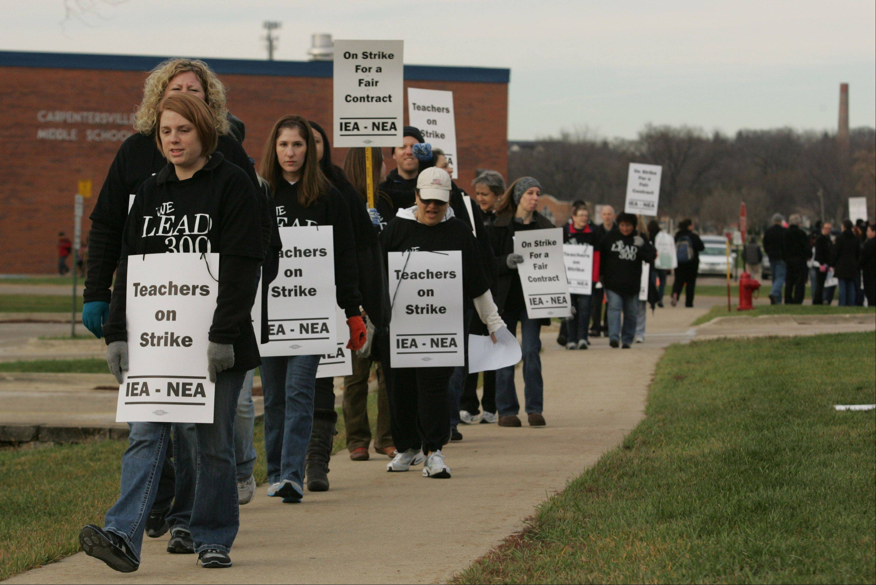 Community Unit District 300 teachers who declined to be identified walk the picket line Tuesday morning near district headquarters and Carpentersville Middle School after the teachers union went on strike.
