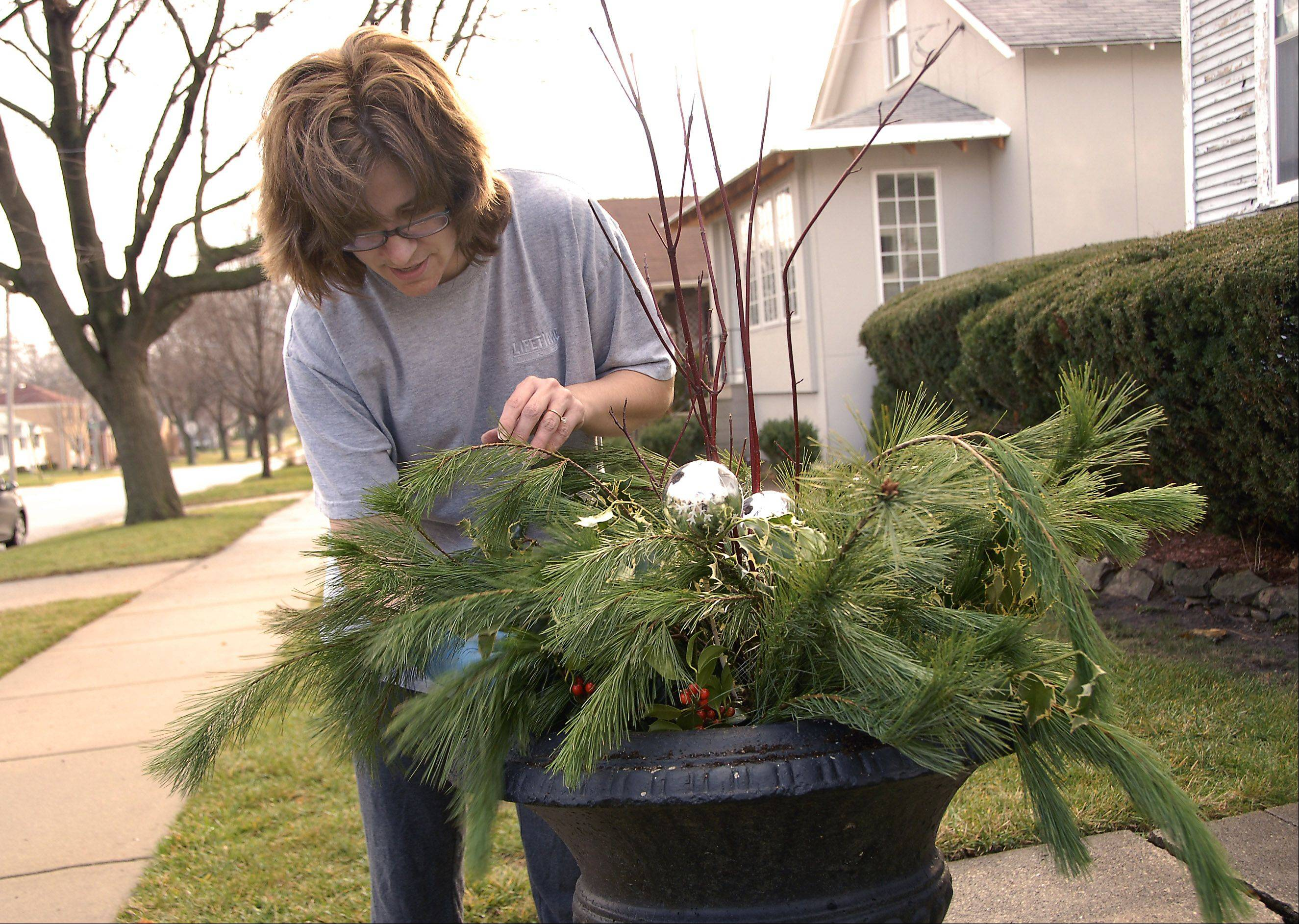 Monica Utyro of Arlington Heights works on her Christmas arrangement in short sleeves on an unseasonably warm December this week. The temperature in front Utyro's home on Vail Avenue was 67 degrees.