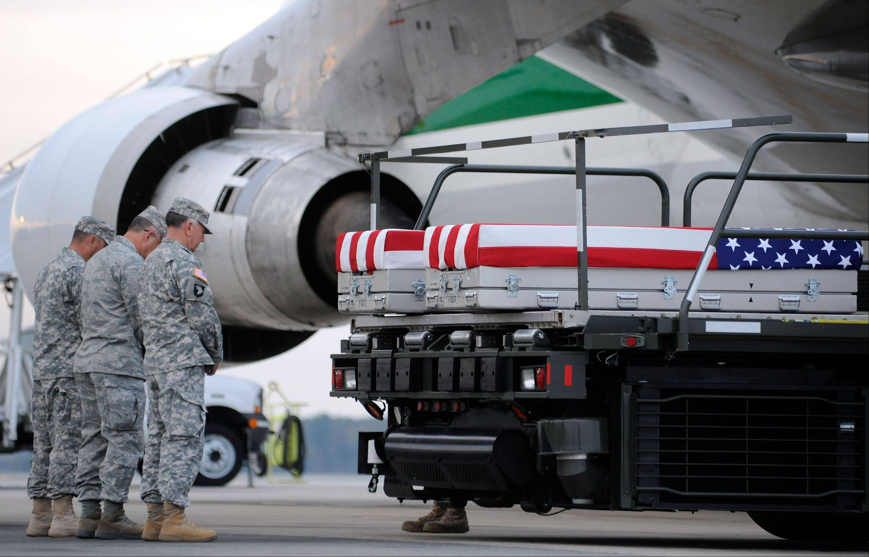 The transfer cases containing the remains of Army Capt. Drew E. Russell, right, and Army Spc. Ricardo Cerros Jr., arrive at Dover Air Force Base in 2011.