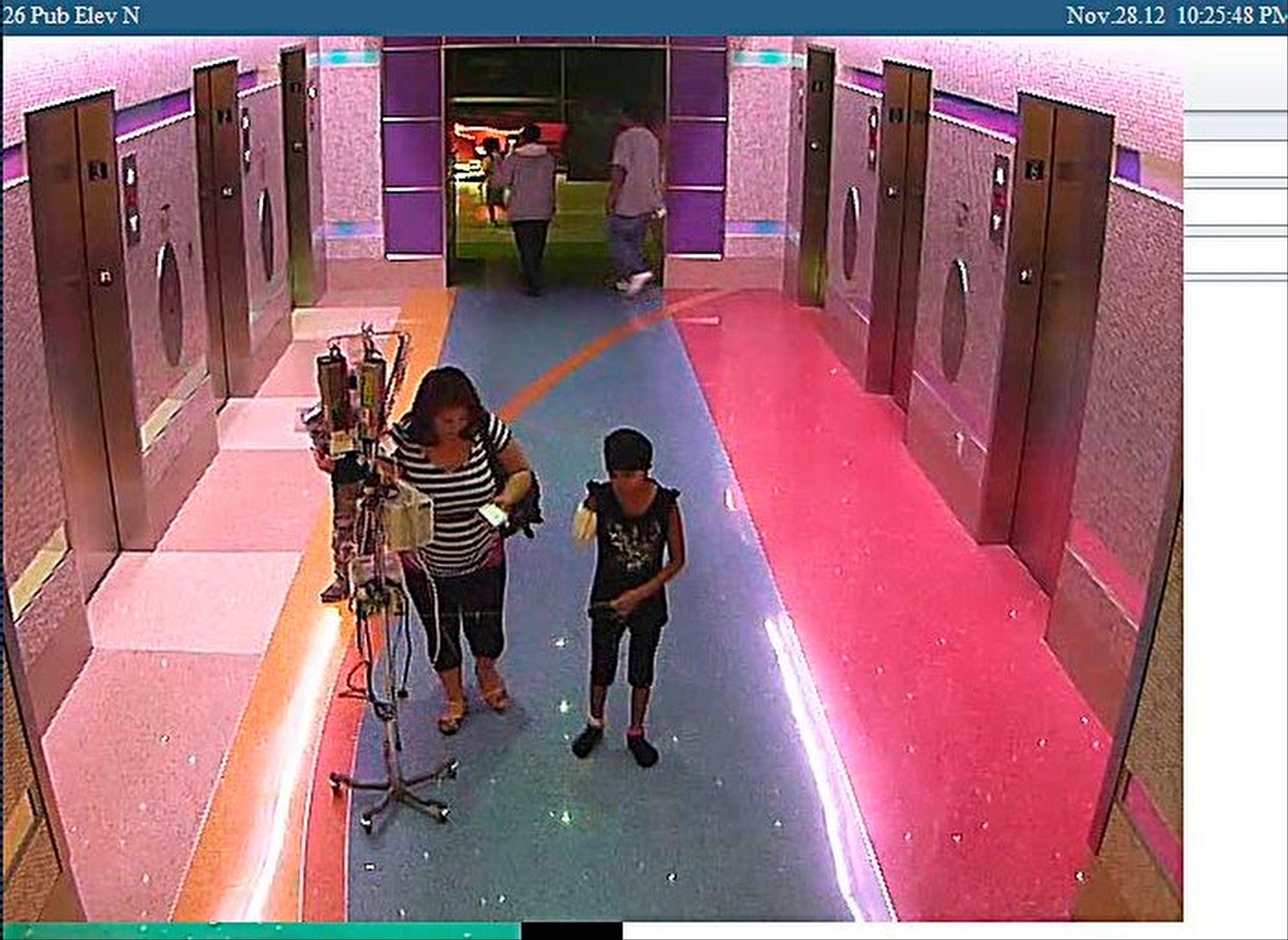 In this hospital surveillance photo released Monday by the Phoenix Police Department, a woman is seen with her 11-year-old daughter, a leukemia patient who had her arm amputated and a heart catheter inserted due to an infection. Authorities say the woman inexplicably took the girl from the hospital last week. Police say that if the catheter is left in too long it could lead to a deadly infection. The family's identity is being withheld but they are calling the girl Emily.