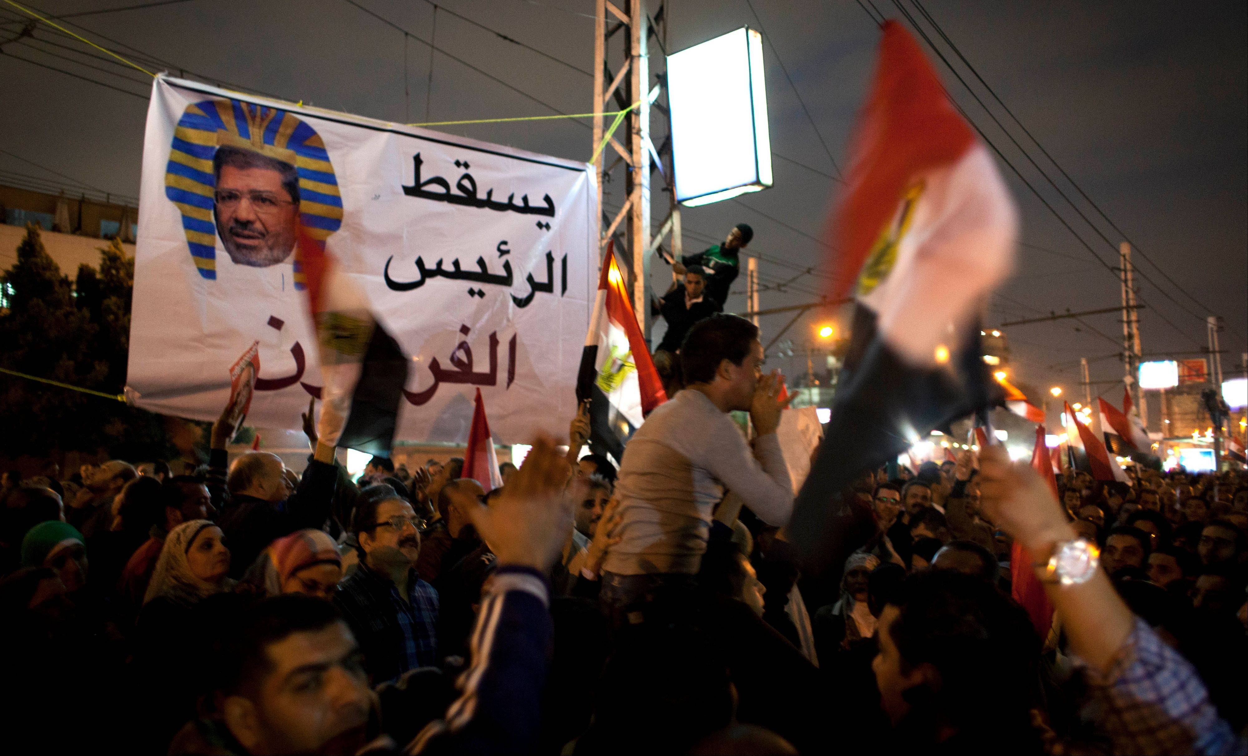 "Protesters carry national flags and chant anti Muslim Brotherhood slogans during a demonstration in front of the presidential palace in Cairo on Tuesday. The protest turned violent as tensions rise over Islamist President Mohammed Morsi's seizure of nearly unrestricted powers and a draft constitution hurriedly adopted by his allies. The Arabic on the banner reads, ""Down with the pharaoh president."""