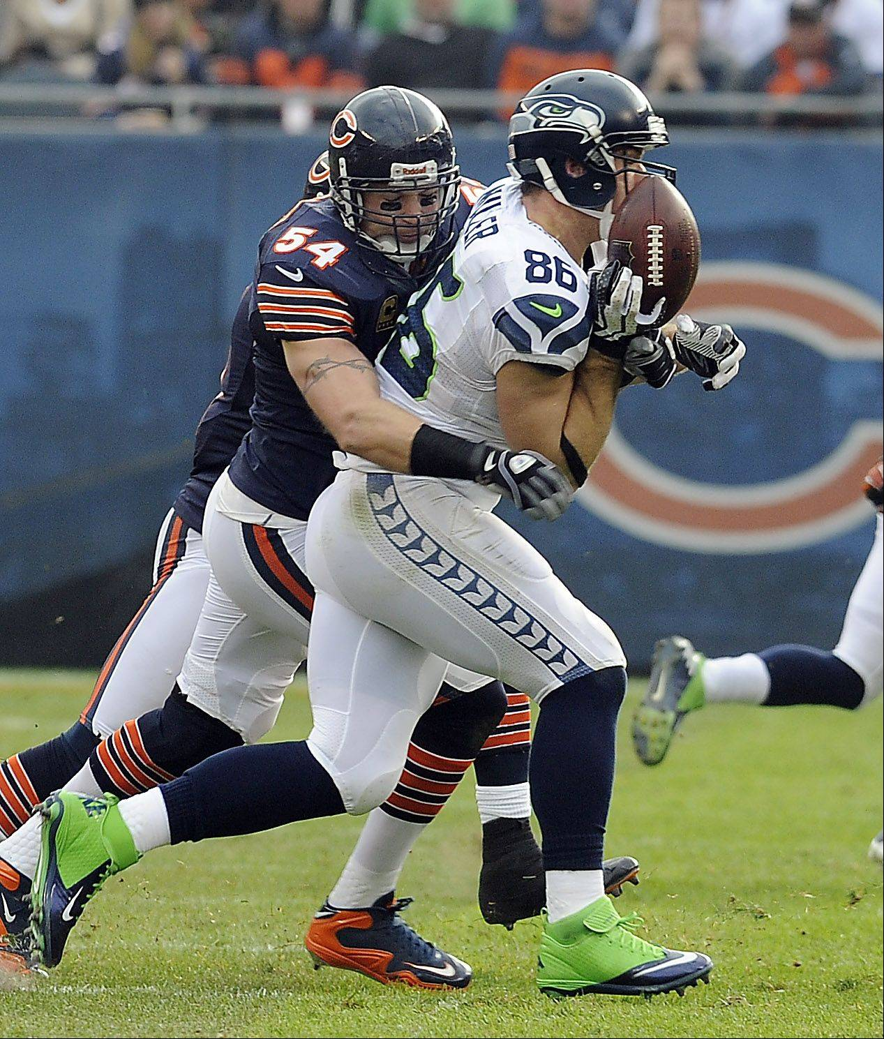 Mark Welsh/mwelsh@dailyherald.comBears Brian Urlacher puts the hit on Seahawks Zach Miller in the second half at Soldier Field in Chicago.
