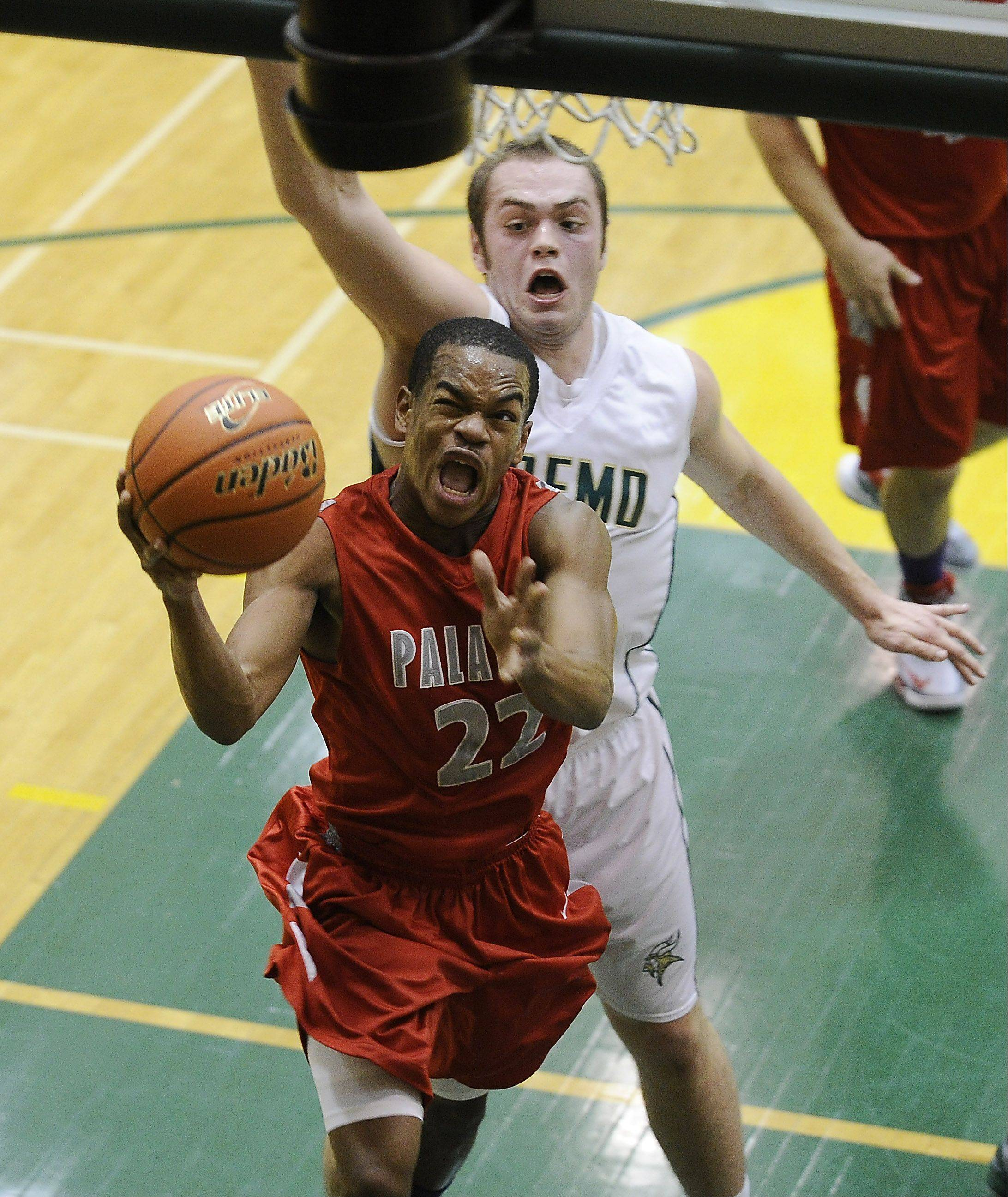 Palatine's Jordan Jarrett drives to the basket under pressure from Fremd's defense during Friday's game at Fremd.