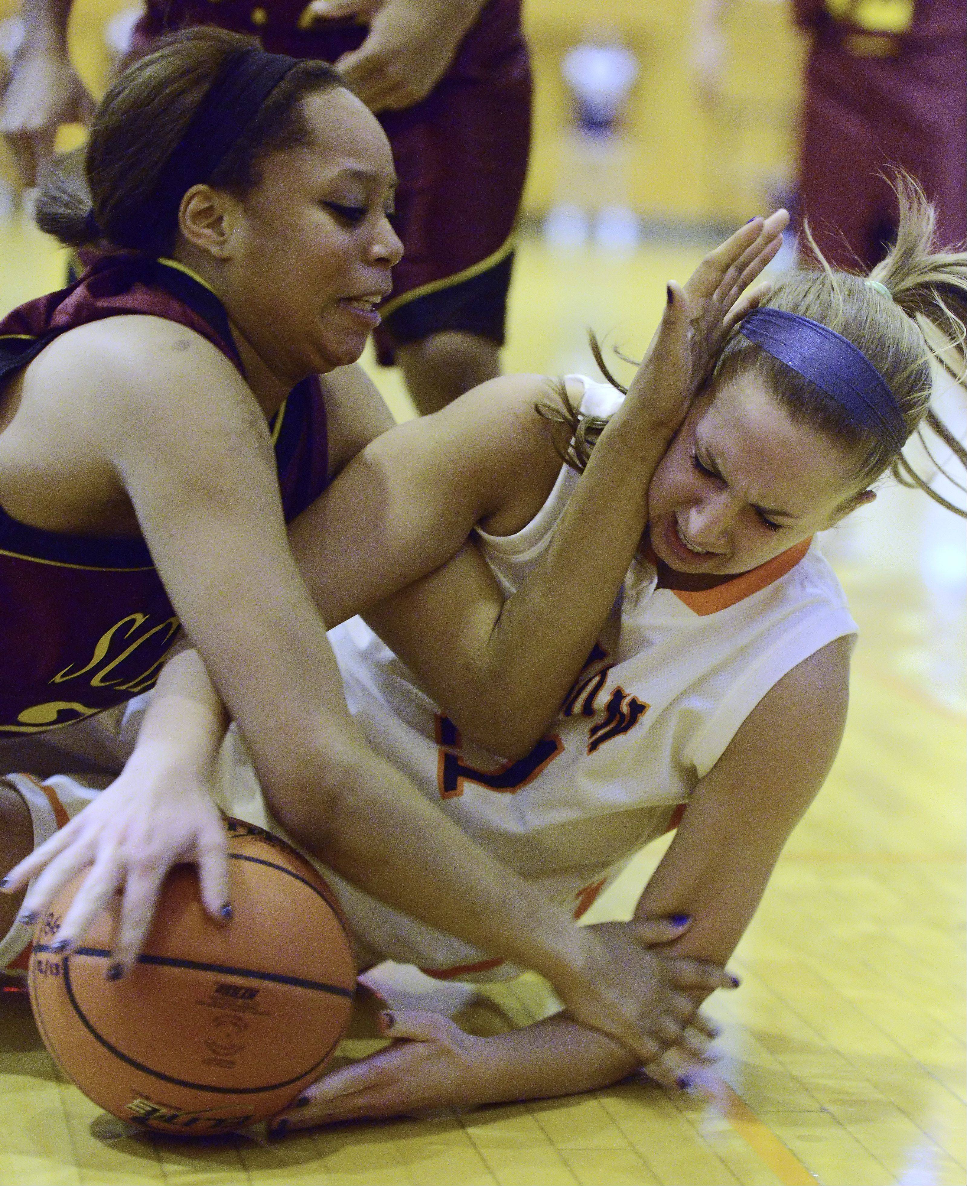 Schaumburg's Jada Blackwell, left, and Buffalo Grove's Amanda Salzman fall to the floor chasing the ball during Tuesday's game.