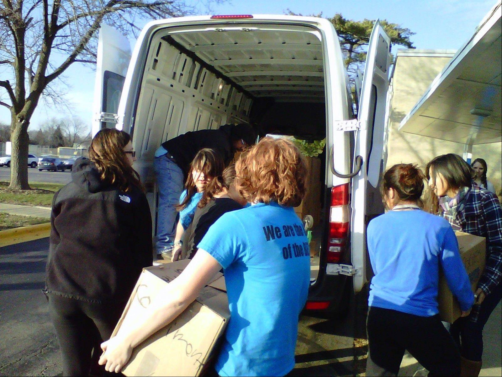Wheeling High School Student Council members help load a van with nonperishable food items for Thanksgiving baskets.