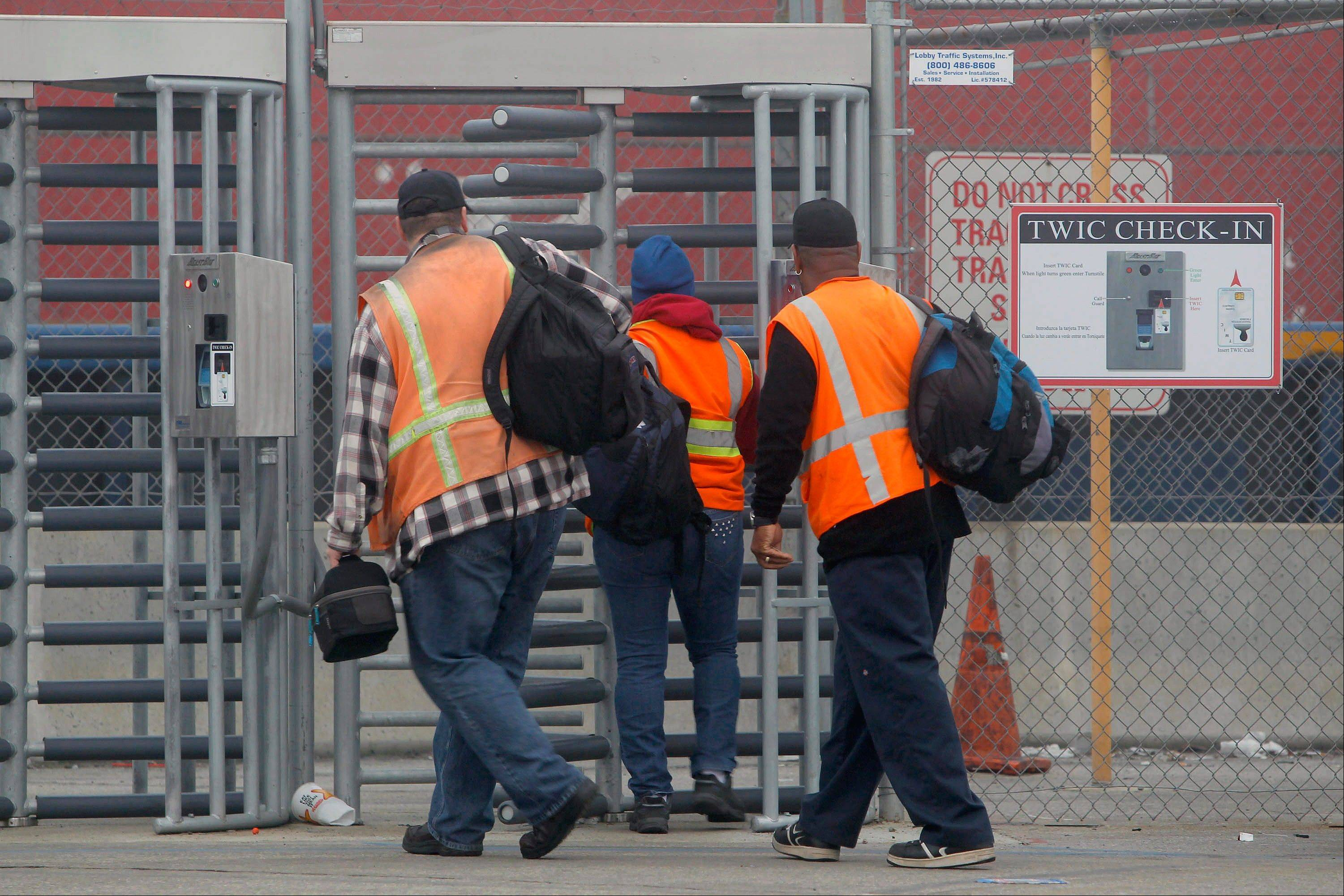 Port workers return to work at the Port of Long Beach Wednesday, Dec. 5, 2012. Work resumed at the Los Angeles and Long Beach harbors after settlement of a strike that crippled the nation�s busiest container port complex for more than a week.