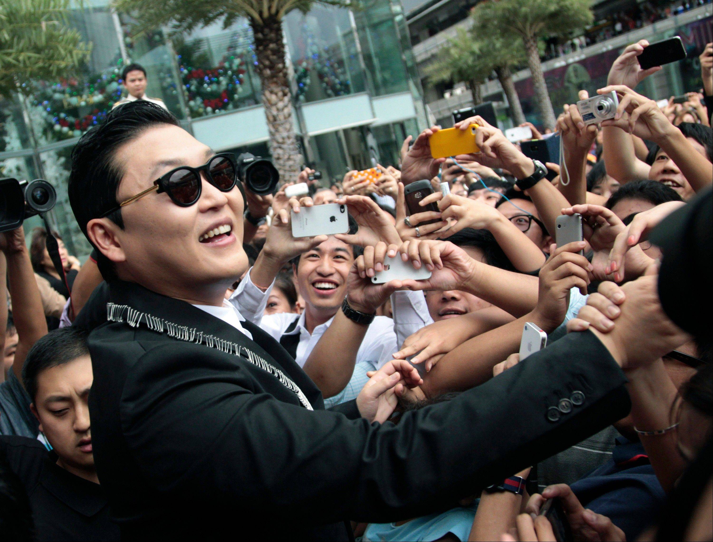 South Korean rapper PSY, who sings the popular �Gangnam Style,� greets Thai fans after a news conference in Bangkok, Thailand. As �Gangnam Style� gallops toward 1 billion views on YouTube, the first Asian pop artist to capture a massive global audience has gotten richer click by click.