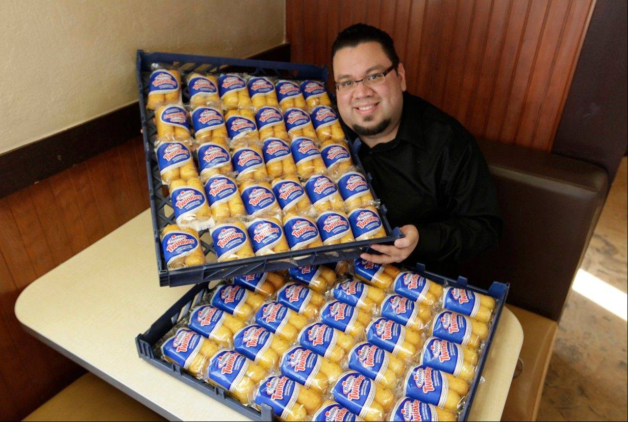 Andres DeLeon of Baby's Steak & Lemonade in Orland Park poses with a large supply of Hostess Twinkies at his restaurant on Wednesda. Baby's Cheesesteak and Lemonade gave away the coveted treats at its locations in Orland Park and Country Club Hills along with 2,200 chocolate cupcakes.