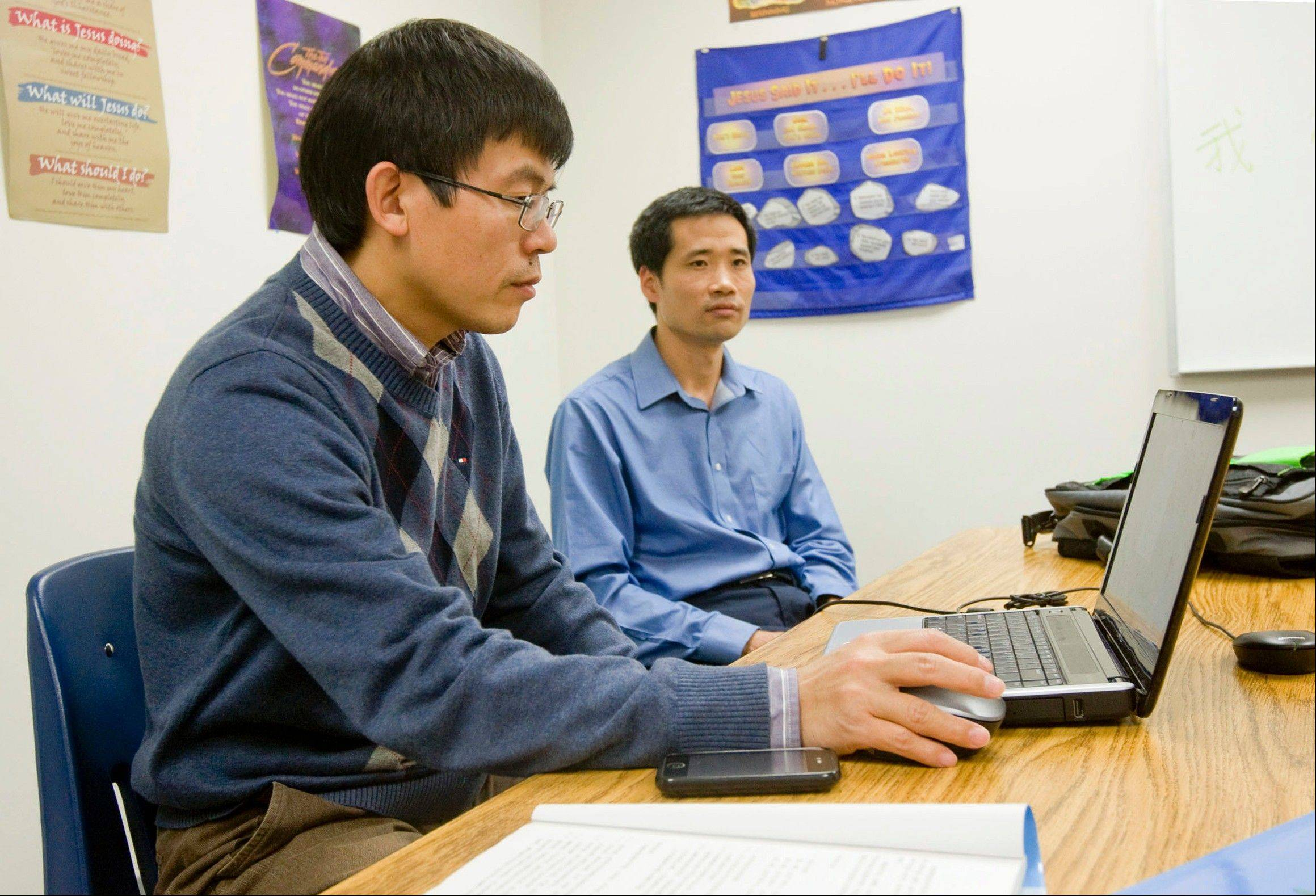 Chinese language instructor Victor Mao, left, works on his laptop as Chris Ma looks on. The two men are involved in a Chinese language class taught over a 10-week period at Moundford Free Methodist Church in Decatur.