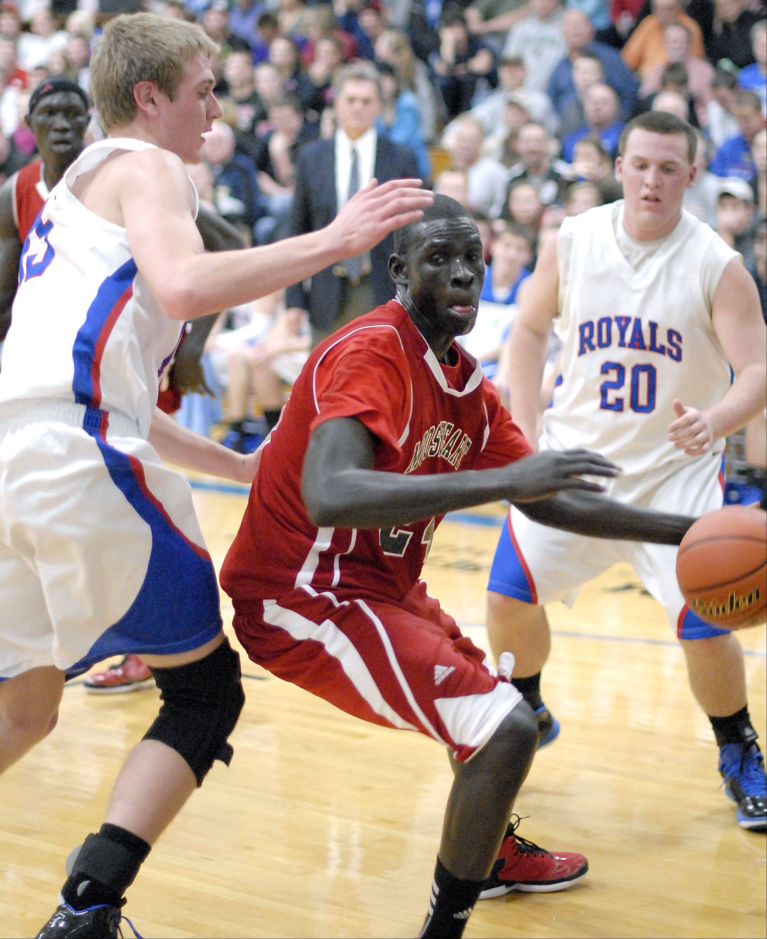 Mooseheart's Mangisto Deng maneuvers around Hinckley-Big Rock's Nick Gentry under the hoop in the first quarter on Wednesday, December 5.