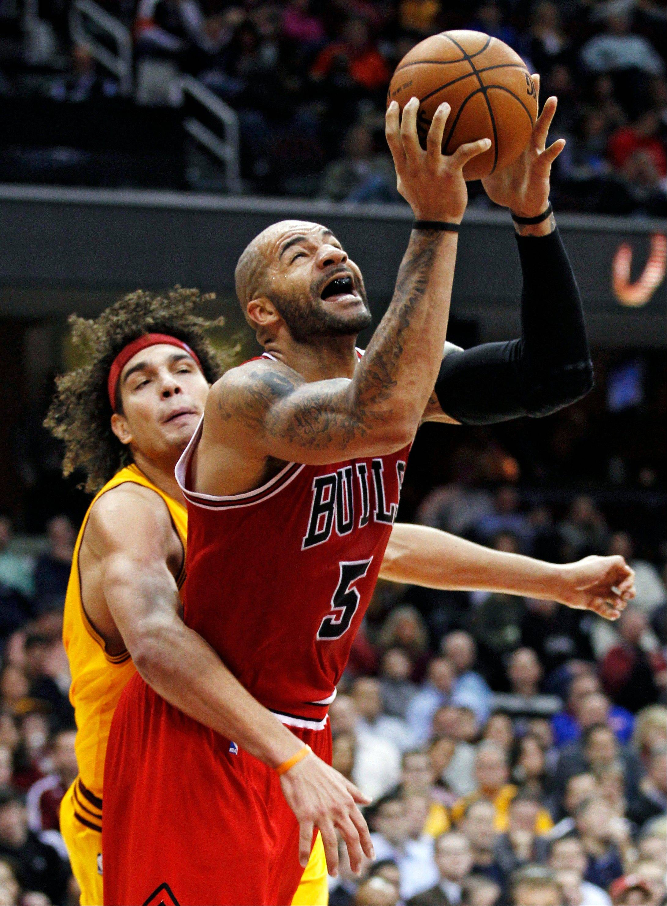 Chicago Bulls' Carlos Boozer (5) is fouled by Cleveland Cavaliers' Anderson Varejao (17), of Brazil, during the third quarter of an NBA basketball game, Wednesday, Dec. 5, 2012, in Cleveland. The Bulls won 95-85. (AP Photo/Tony Dejak)