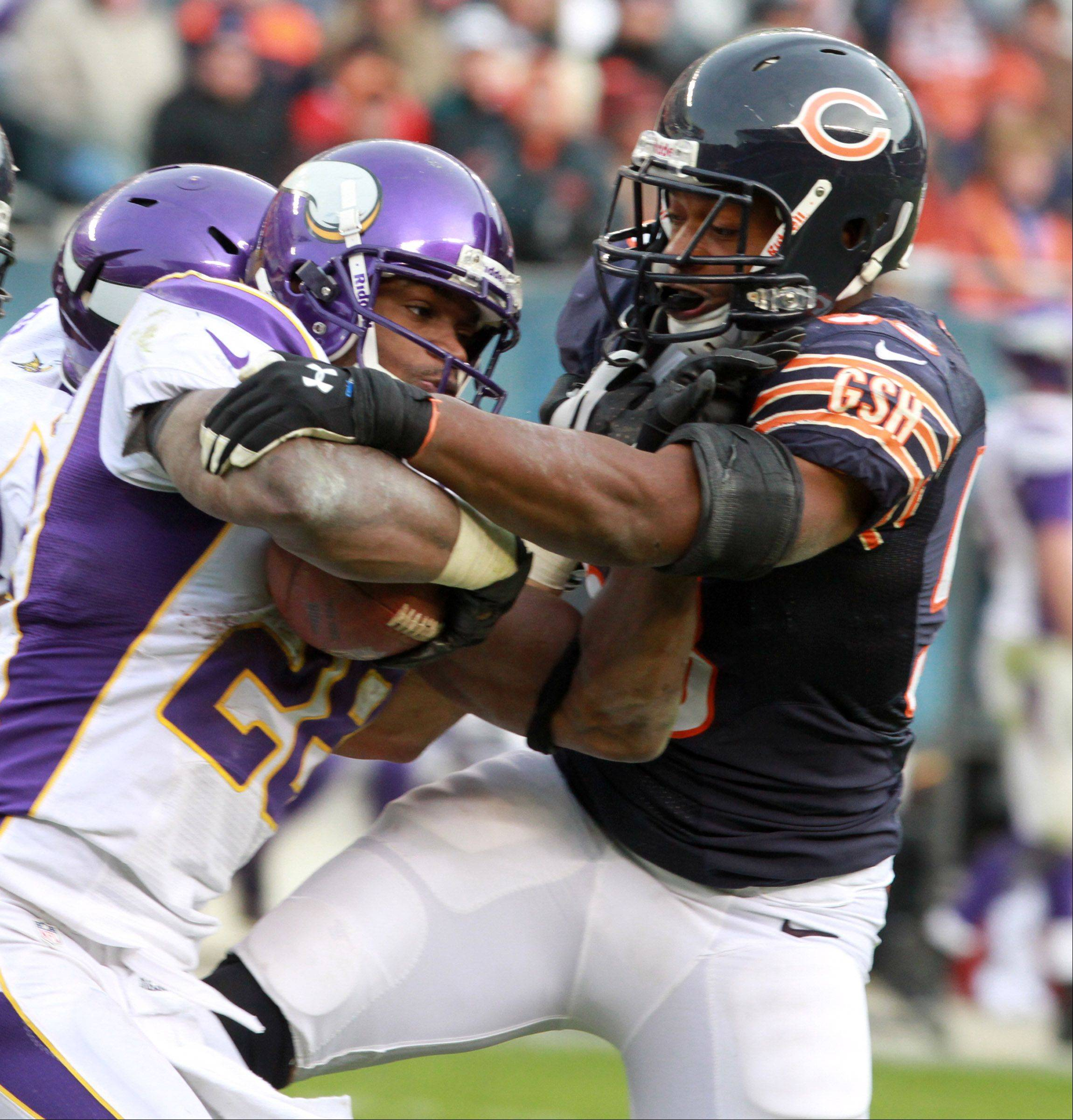 Minnesota Vikings Adrian Peterson escapes from Chicago Bears Nick Roach for extra yardage at Soldier Field Sunday.