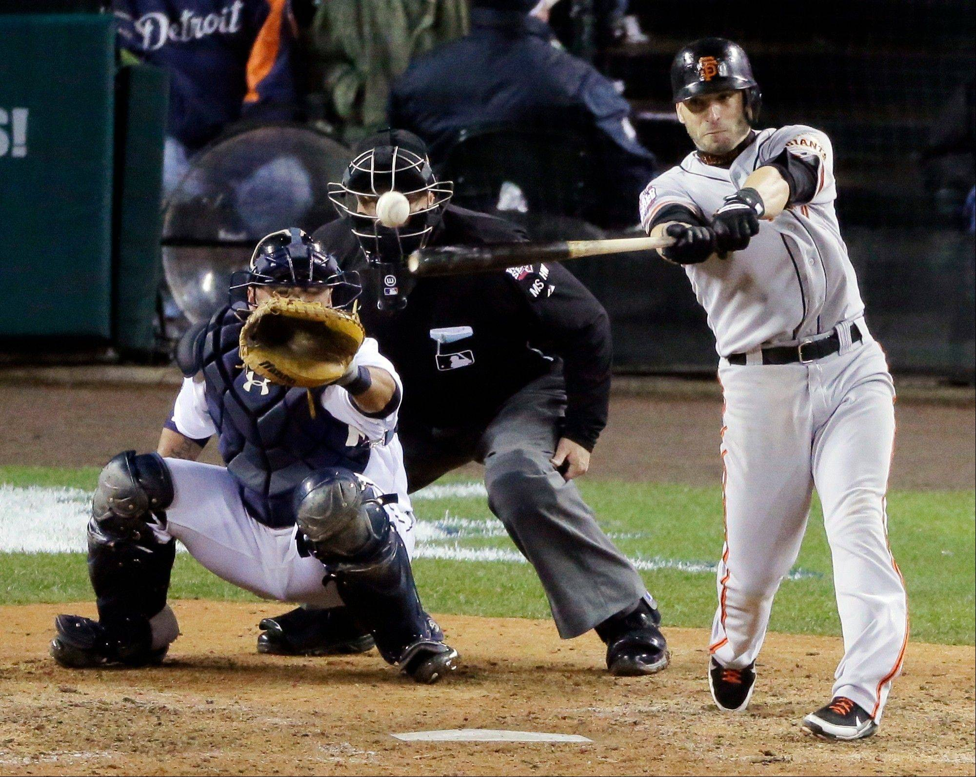 The San Francisco Giants� Marco Scutaro hits an RBI single during the 10th inning of Game 4 the World Series against the Detroit Tigers in Detroit. Two people with knowledge of the negotiations said Tuesday that Scutaro is weighing a two-year contract offer from the Giants that includes a vesting option.