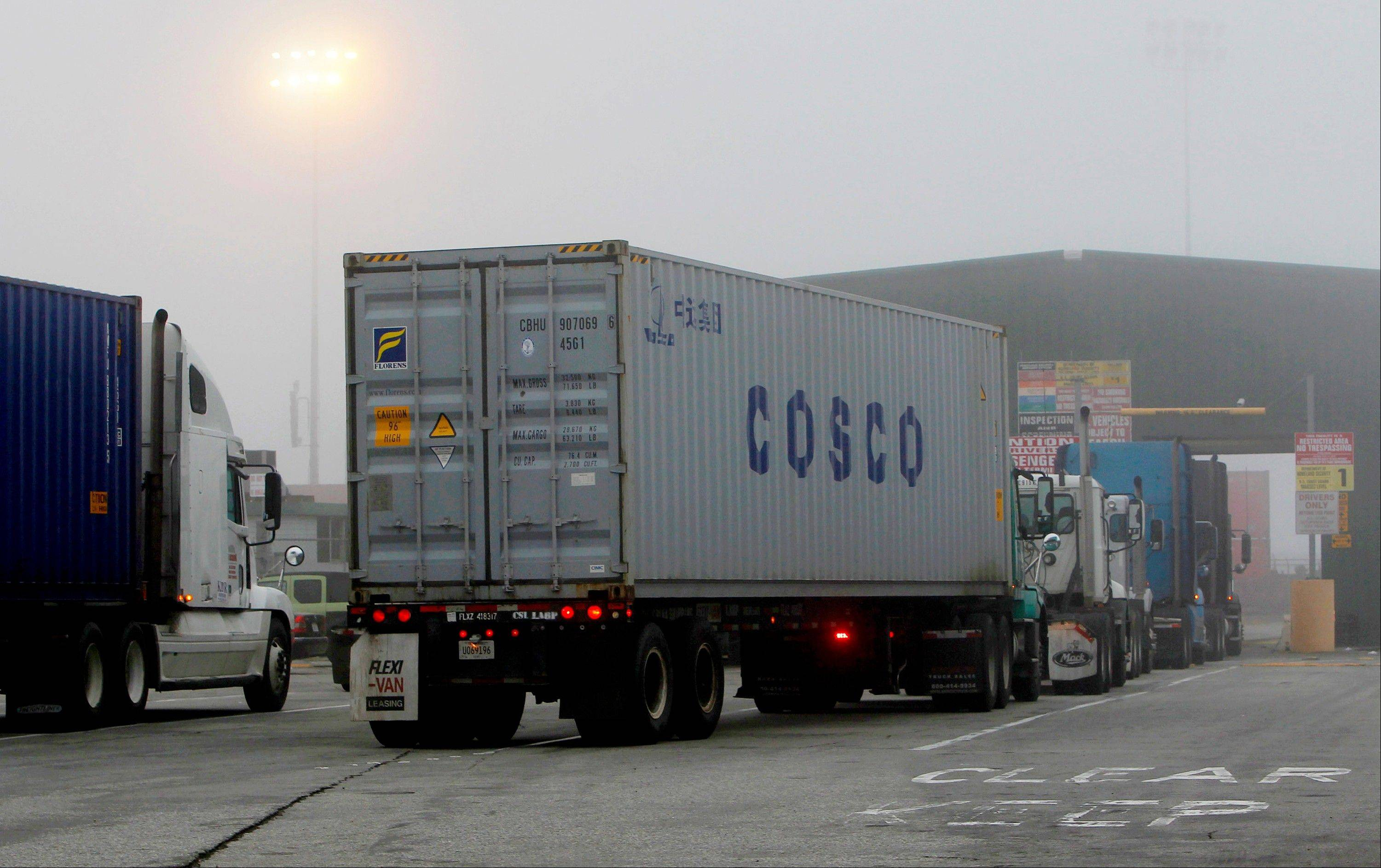 Cargo trucks line up in the dense fog to enter the Port of Long Beach Wednesday December 5, 2012. Work resumed Wednesday at the Los Angeles and Long Beach harbors after settlement of a strike that crippled the nation's busiest container port complex for more than a week.