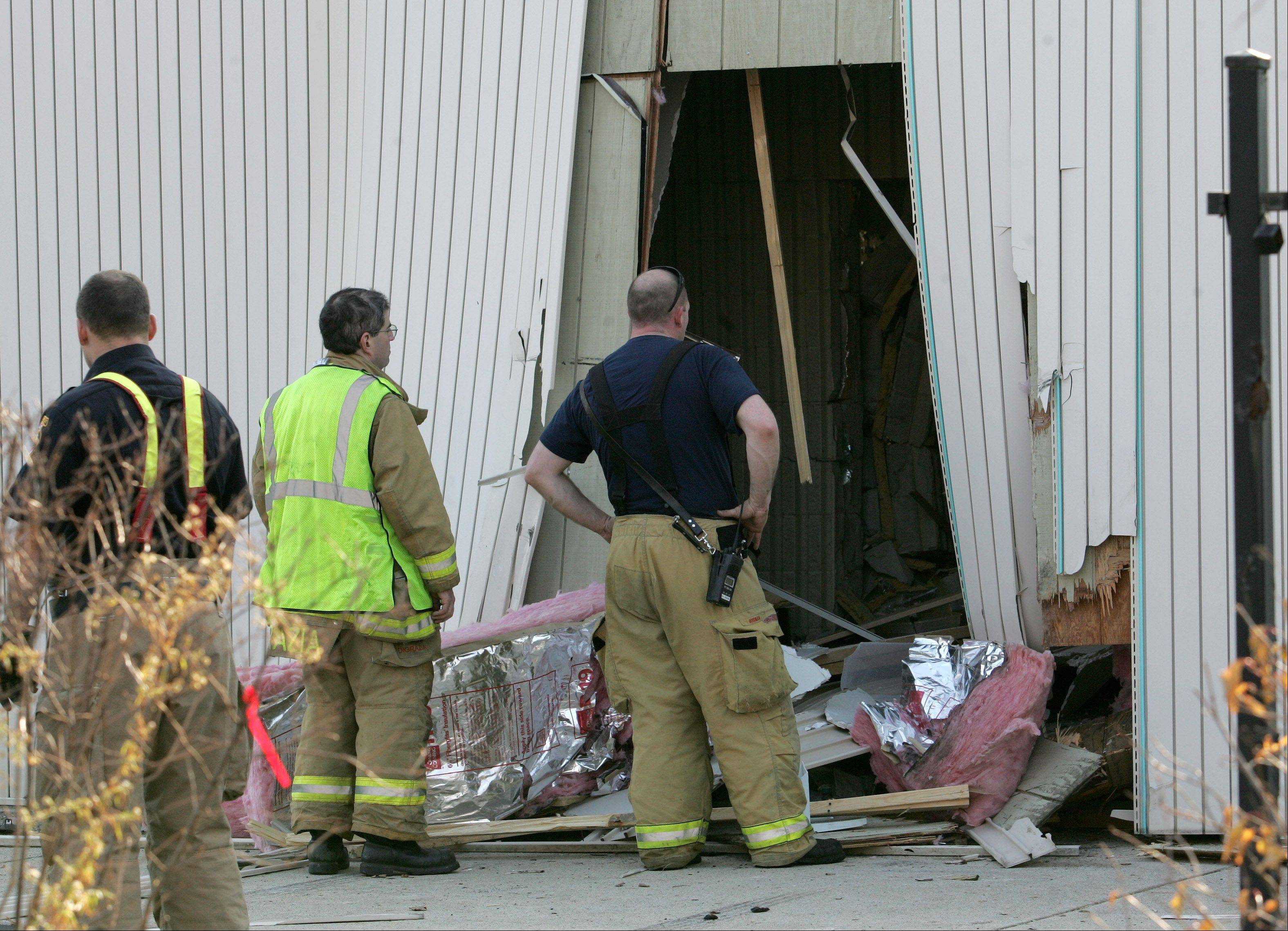 Firefighters investigate the scene where a car crashed into Rosin Eyecare on Ogden Avenue in Naperville last Friday. Police say just a day earlier the same motorist crashed through a fence and into a back yard a block away.