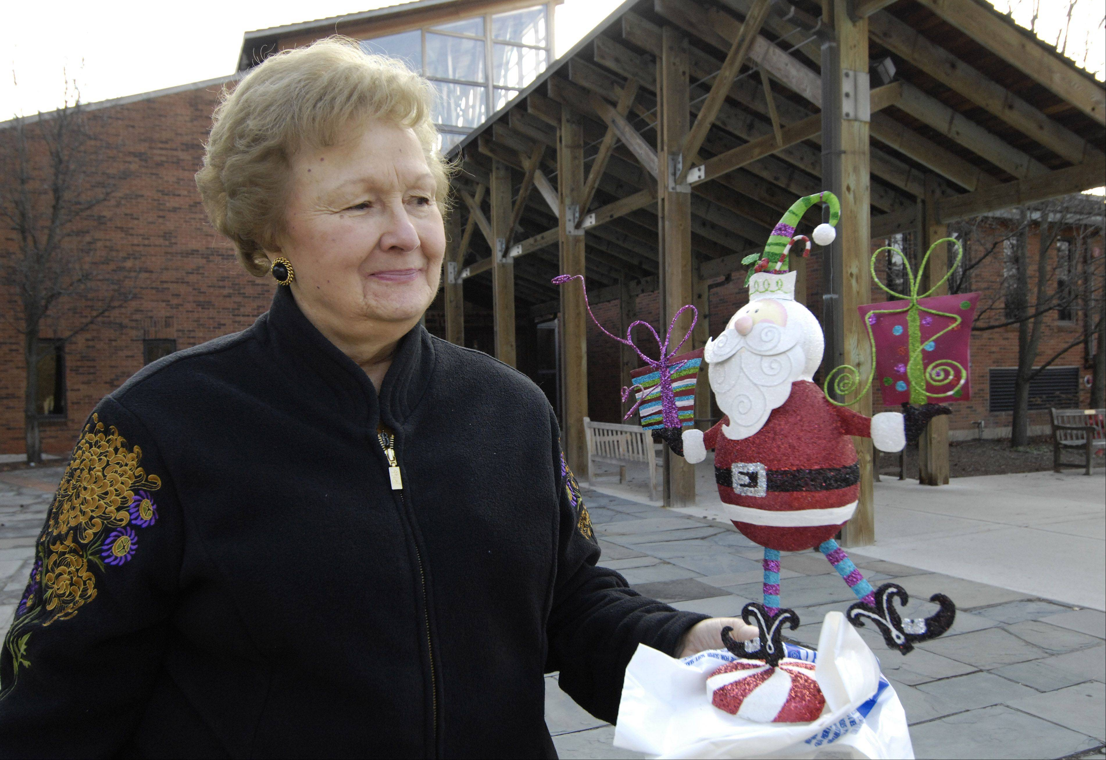 JOE LEWNARD/jlewnard@dailyherald.com Barbara Germain of the Countryside Garden Class of Barrington carries a Santa figure she said the Barrington Area Library rejected last month when she dropped it off for inclusion in a holiday display.