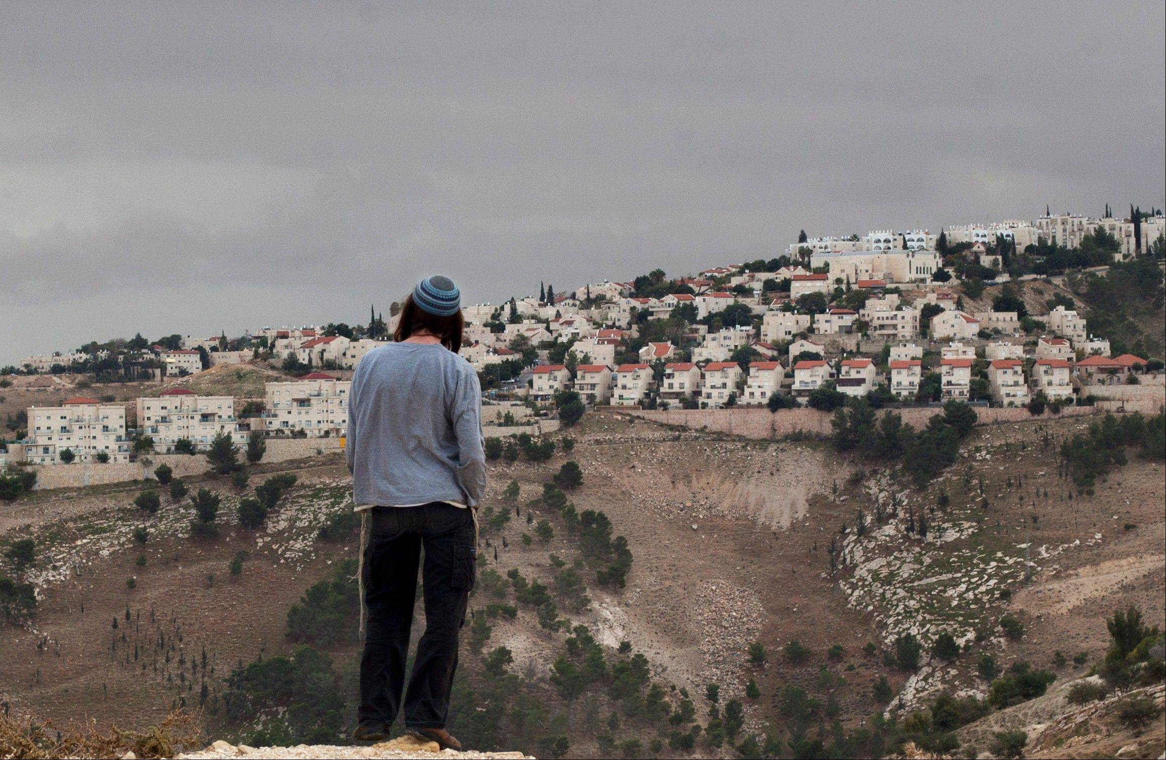 A Jewish settler looks at the West bank settlement of Maaleh Adumim, from the E-1 area on the eastern outskirts of Jerusalem, Wednesday, Dec. 5, 2012. An Israeli-Palestinian showdown over plans for new Jewish settlements around Jerusalem escalated on Wed