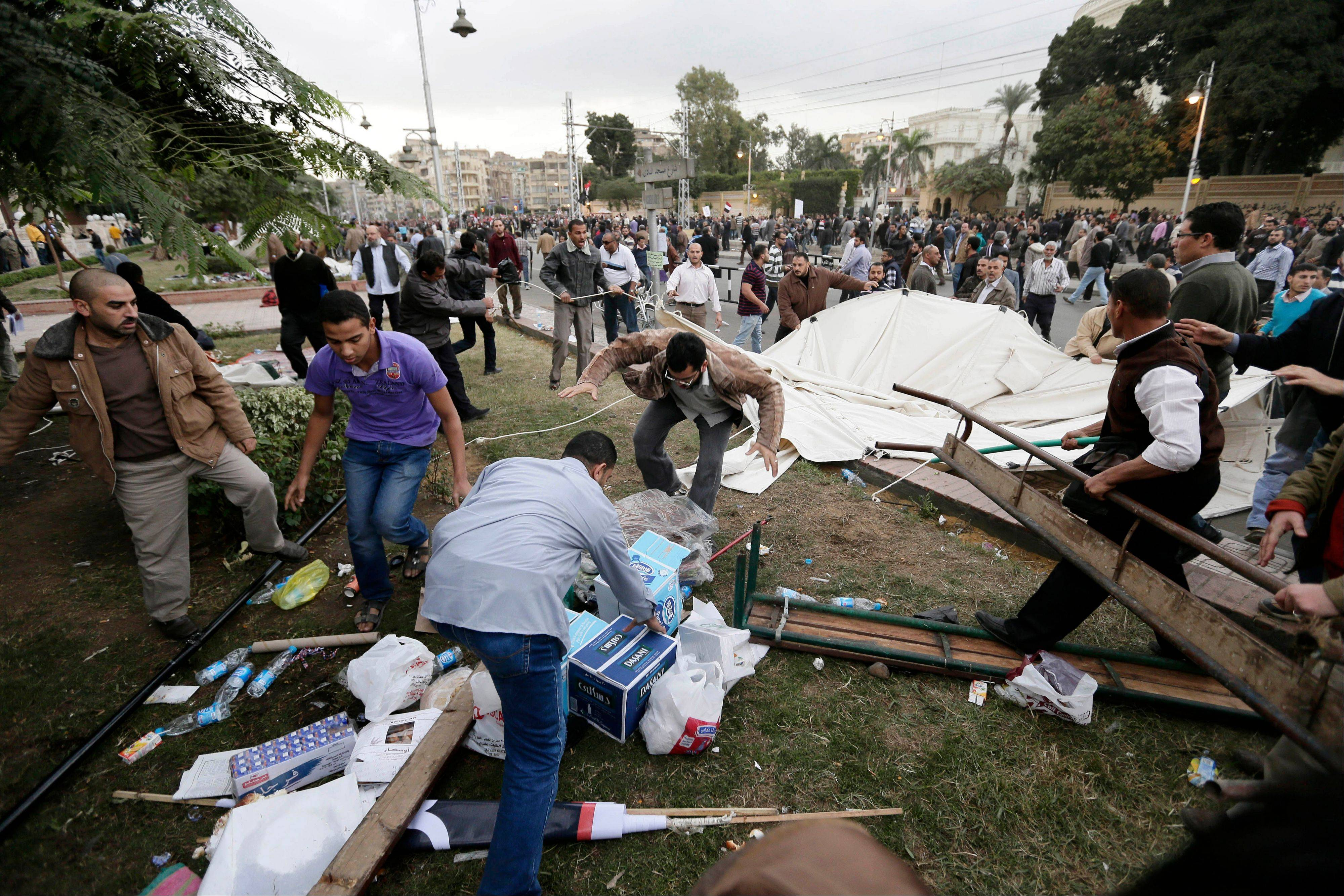 Supporters of Egyptian President Mohammed Morsi remove tents of opposition protesters outside the presidential palace in Cairo Wednesday. Supporters of Morsi and opponents clashed outside the presidential palace.