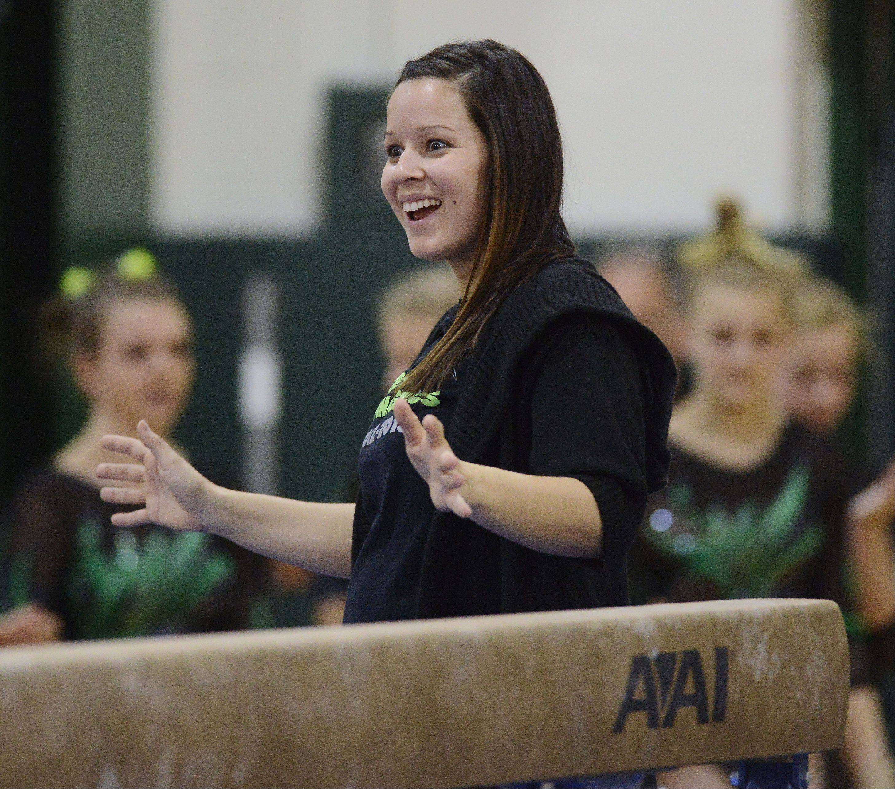 Fremd girls gymnastics coach Elise Ference celebrates a team member's success on the balance beam.