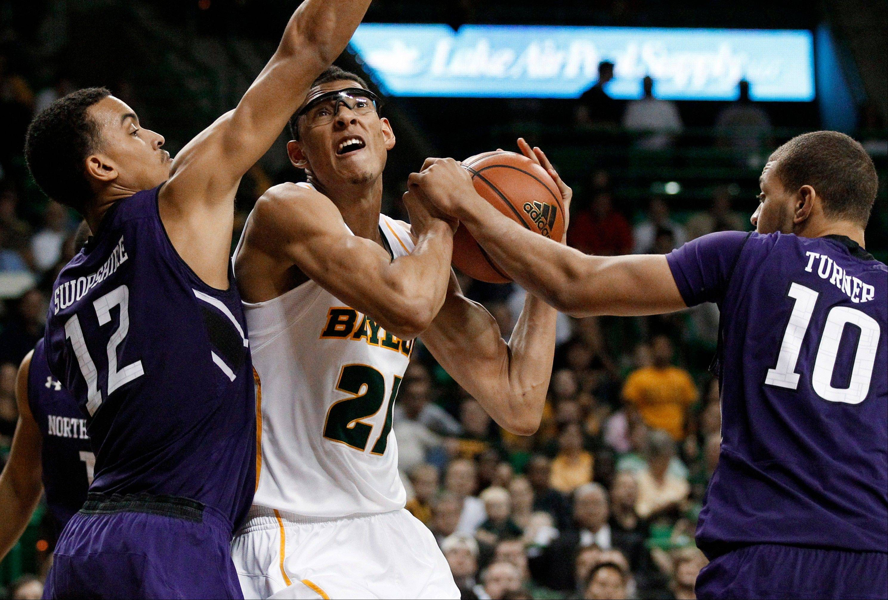 Northwestern's Jared Swopshire (12) and Mike Turner (10) combine to stop a drive to the basket by Baylor's Isaiah Austin (21) in the second half Tuesday in Waco, Texas. Northwestern defeated Baylor 74-70.