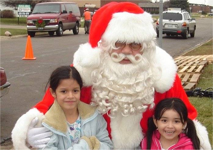 Two needy children served by HSP's program meeting Santa Claus.