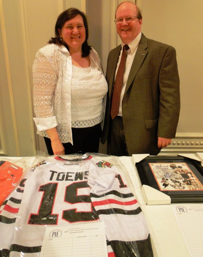 Pictured with some of the auction items is PIE chairperson Donna Cain with David Cain, who served as the master of ceremonies for the PIE event. David Cain is a member of the Board of Education in School District 45.