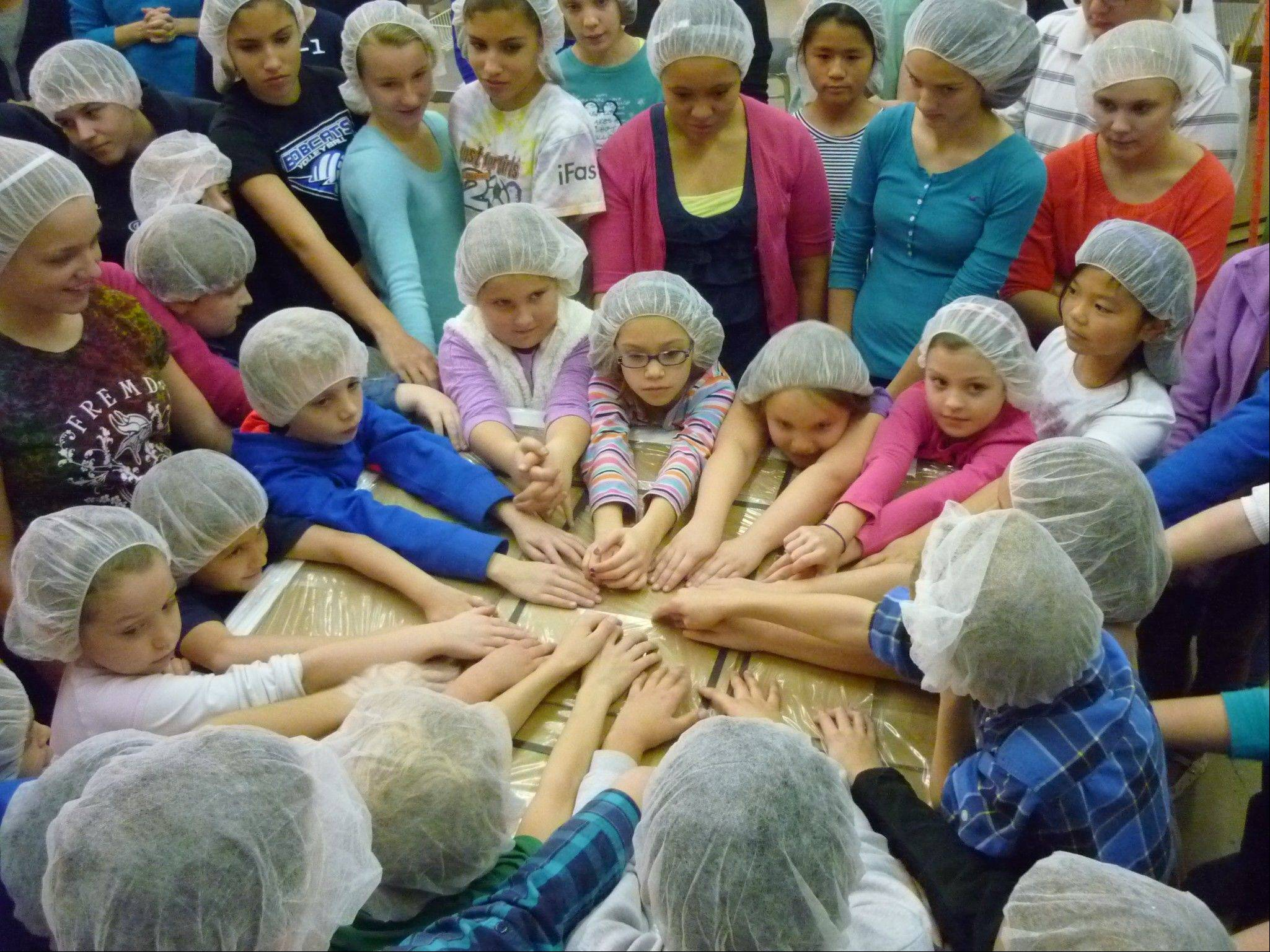 After boxing the food packets, students at Immanuel Lutheran School in Palatine pray that the food packets they prepared arrives safely in Swaziland, Africa, and nourishes the bodies of the children receiving the food.