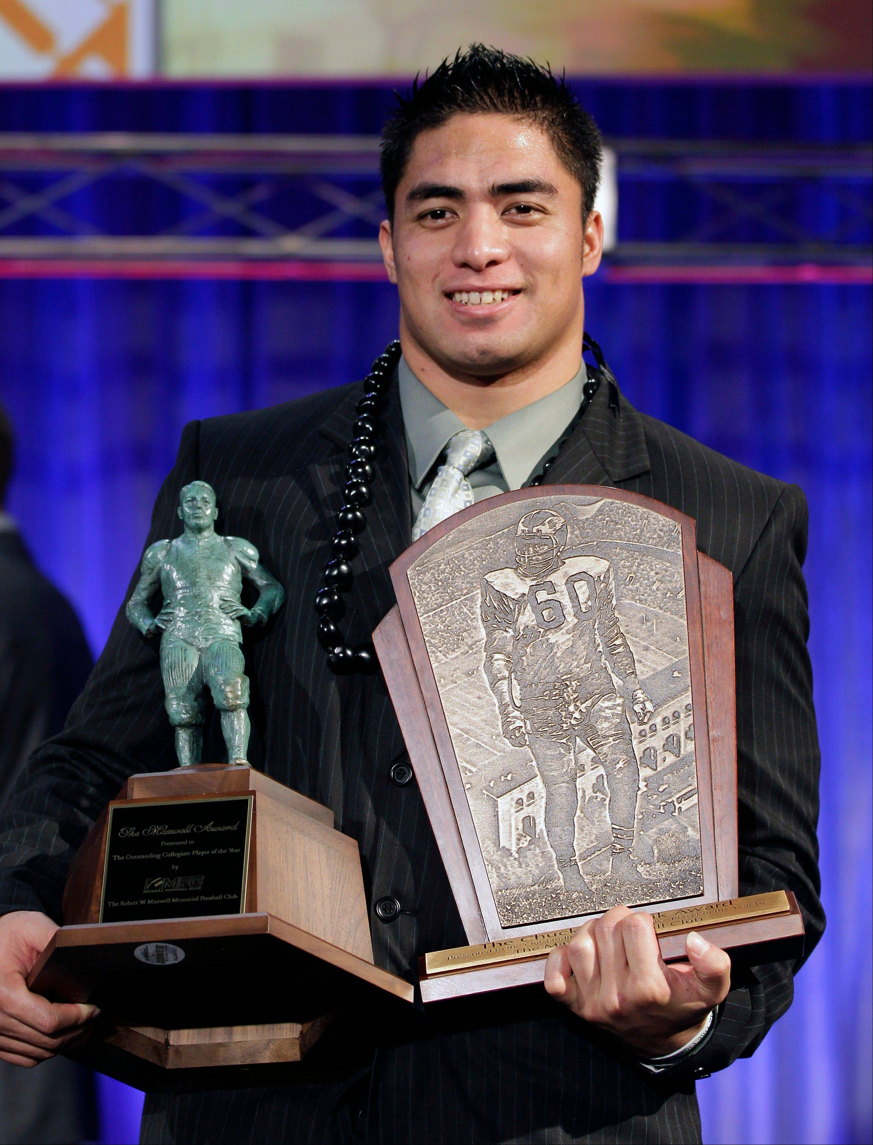 Notre Dame defensive back Manti Te'o displays his trophies after being named the college defensive player of the year and the nation's college player of the year Thursday at the Home Depot College Football Awards in Lake Buena Vista, Fla.