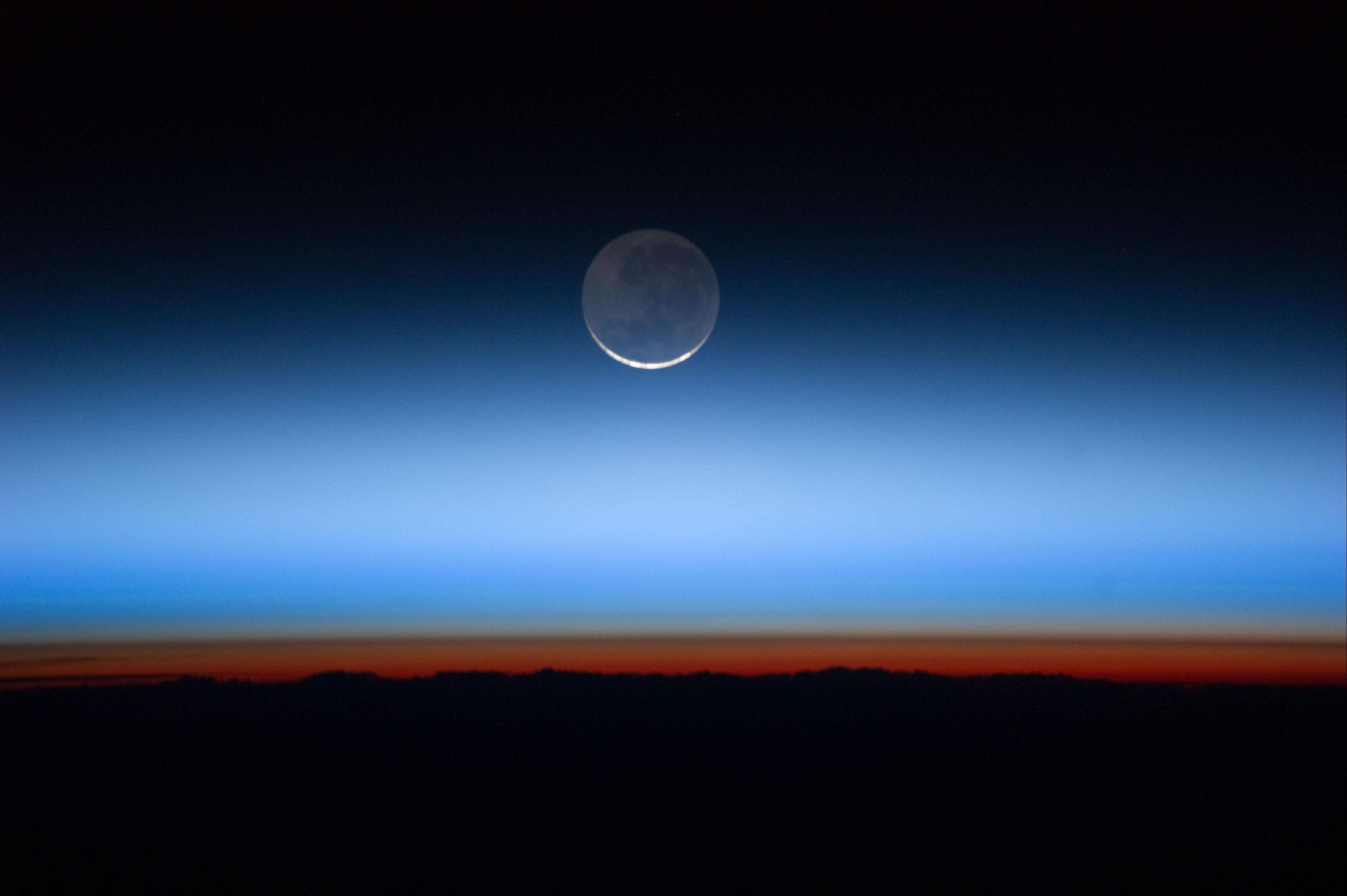This undated image made available by NASA and photographed by the Expedition 28 crew aboard the International Space Station, shows the moon, at center with the limb of Earth near the bottom transitioning into the orange-colored troposphere, the lowest and most dense portion of the Earth's atmosphere.
