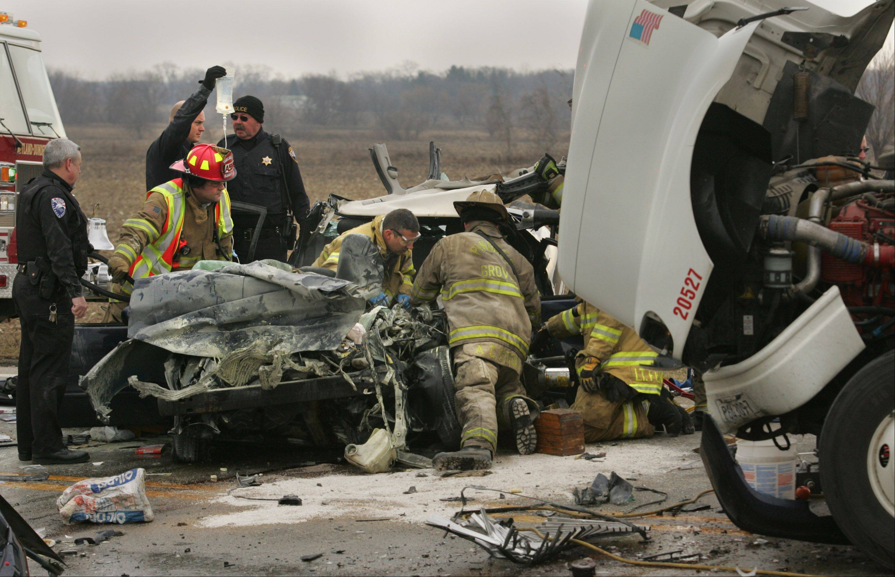 First responders from several area departments work to extricate Martin Baureis, 26, of Johnsburg, from his car Thursday in unincorporated Rutland Township. Sheriff's police said the car Baureis was driving veered into the path of an oncoming semitrailer and was hit head-on just east of Route 72 and Big Timber Road.