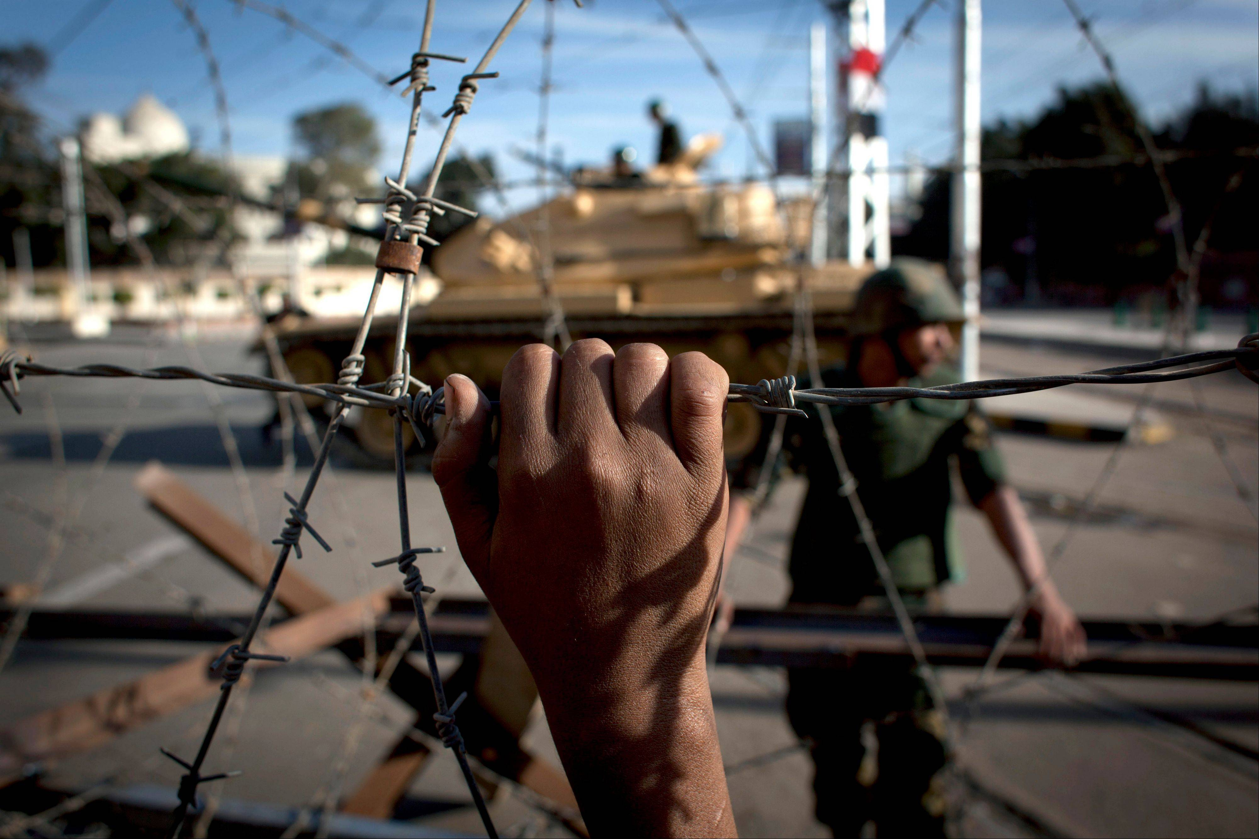 An Egyptian army tank is seen behind barbed wire securing the perimeter of the presidential palace while protesters on the other side chant anti President Mohammed Morsi slogans, in Cairo, Egypt, Thursday, Dec. 6, 2012. The Egyptian army deployed tanks and gave both supporters and opponents of Mohammed Morsi a deadline to leave the area outside the presidential palace Thursday following fierce street battles that left several people dead and hundreds injured.
