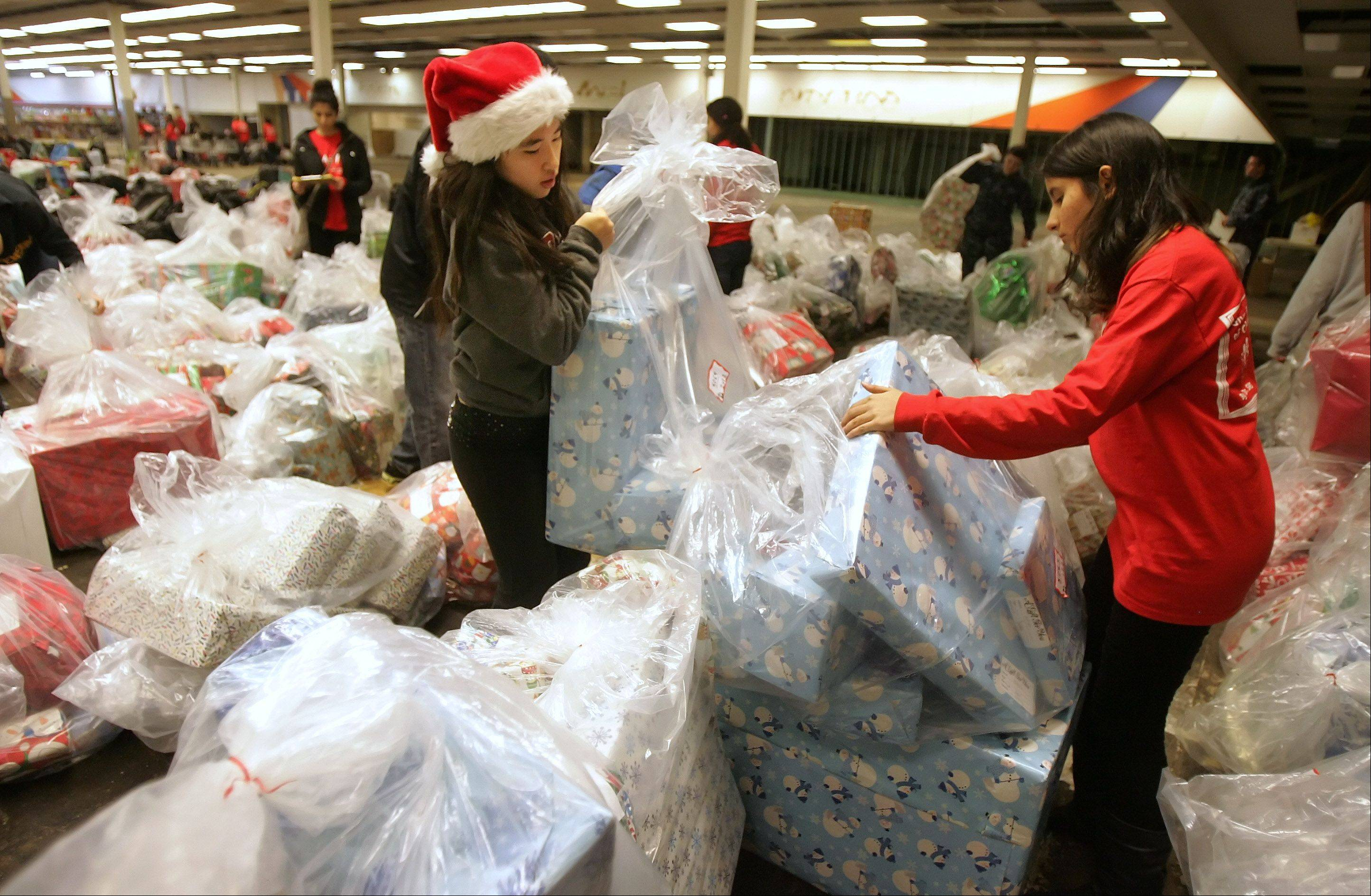 Juniors Stephanie Li, left, and Lily Barghi sort presents by family as Stevenson High School students deliver toys and gifts Wednesday for Catholic Charities' Lake County Adopt-A-Family Christmas Gift Program to the gift warehouse in Waukegan.