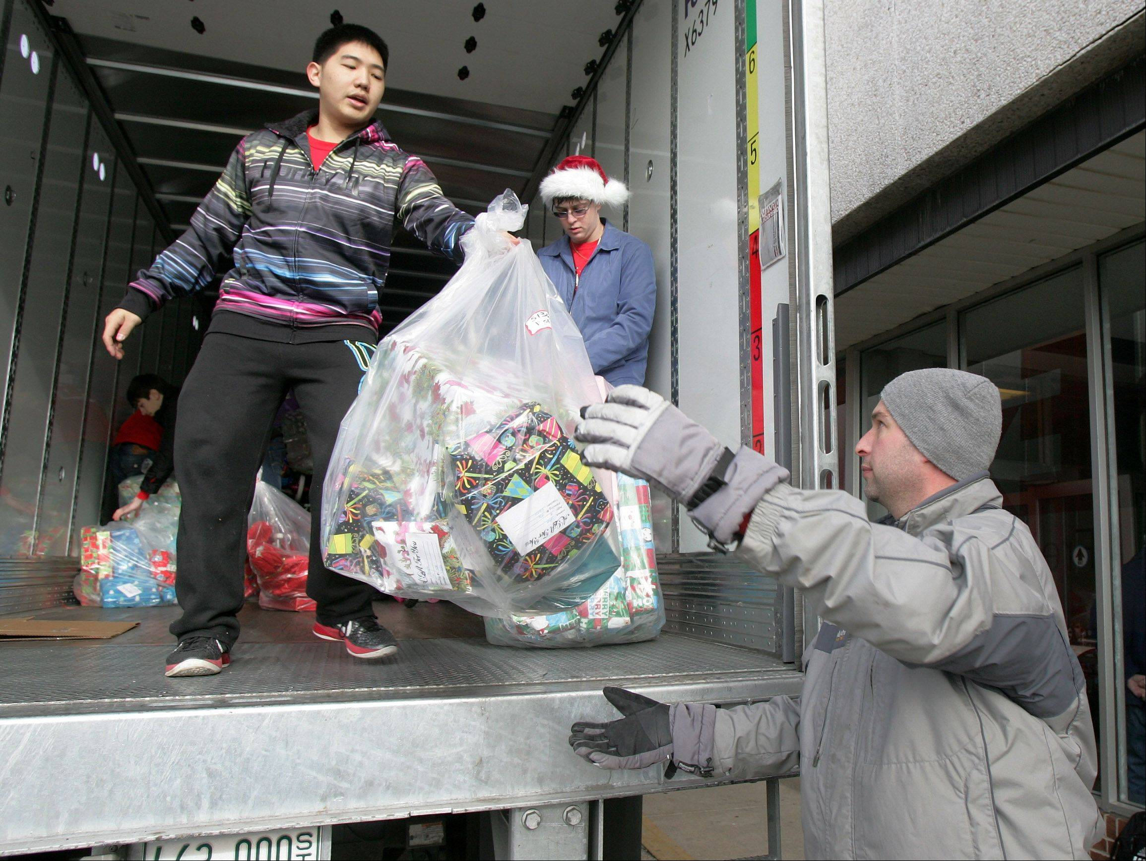 Senior Kevin Xu unloads presents from a truck to Ted Goergen, director of student activities, as Stevenson High School students deliver toys and gifts Wednesday to Catholic Charities' Lake County Adopt-A-Family Christmas Gift Program. The gifts will benefit about 235 families.