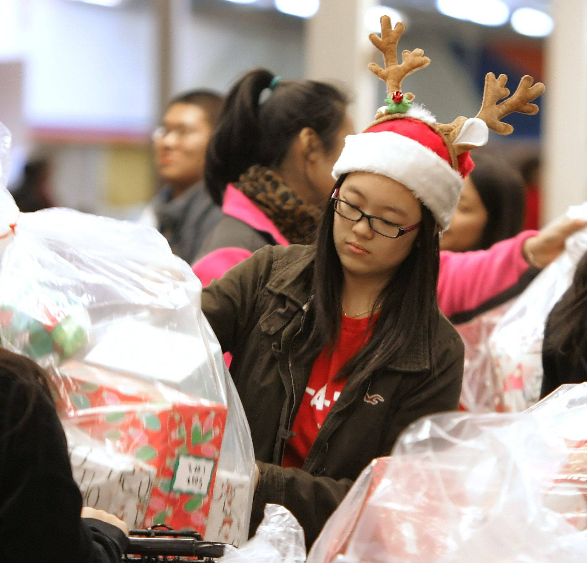 Stevenson High School senior Christine Zhal gets in the holiday spirit by wearing antlers while unloading presents Wednesday.
