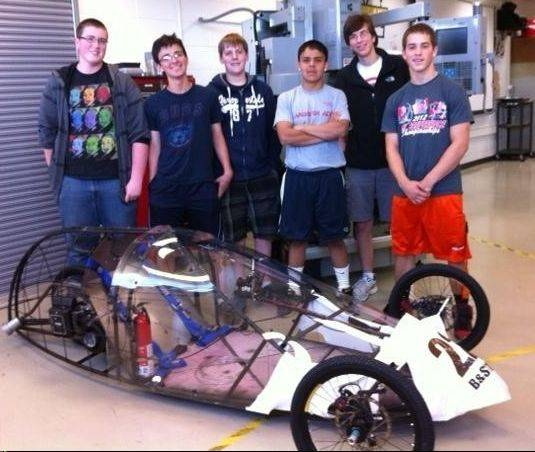 Alex Baratta, far right, and some of his Hersey High School classmates stand with the high-mileage vehicle they designed and built.