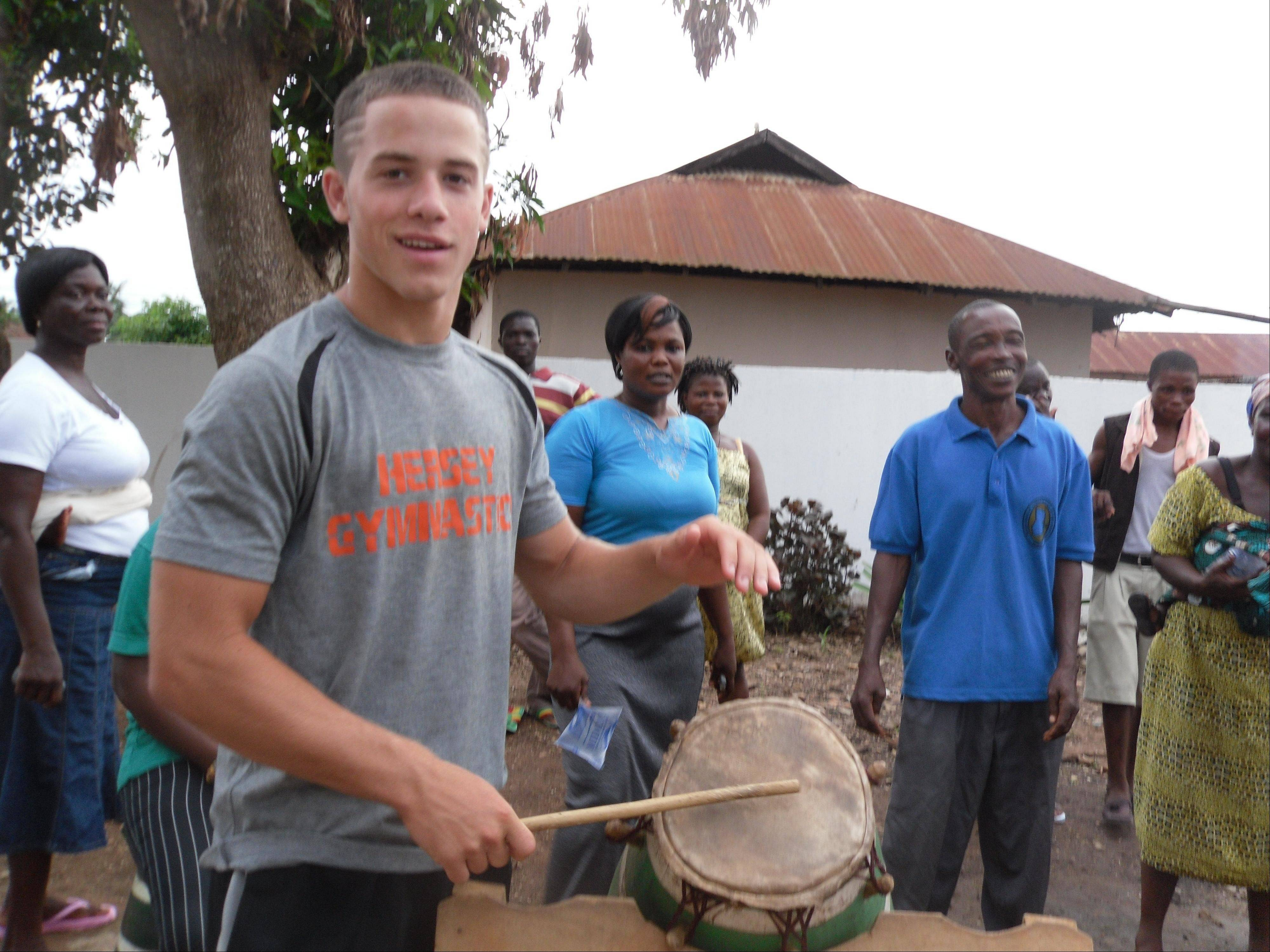 Hersey High School student Alex Baratta, 17, takes part in a traditional drum ceremony during a volunteer trip to Ghana.