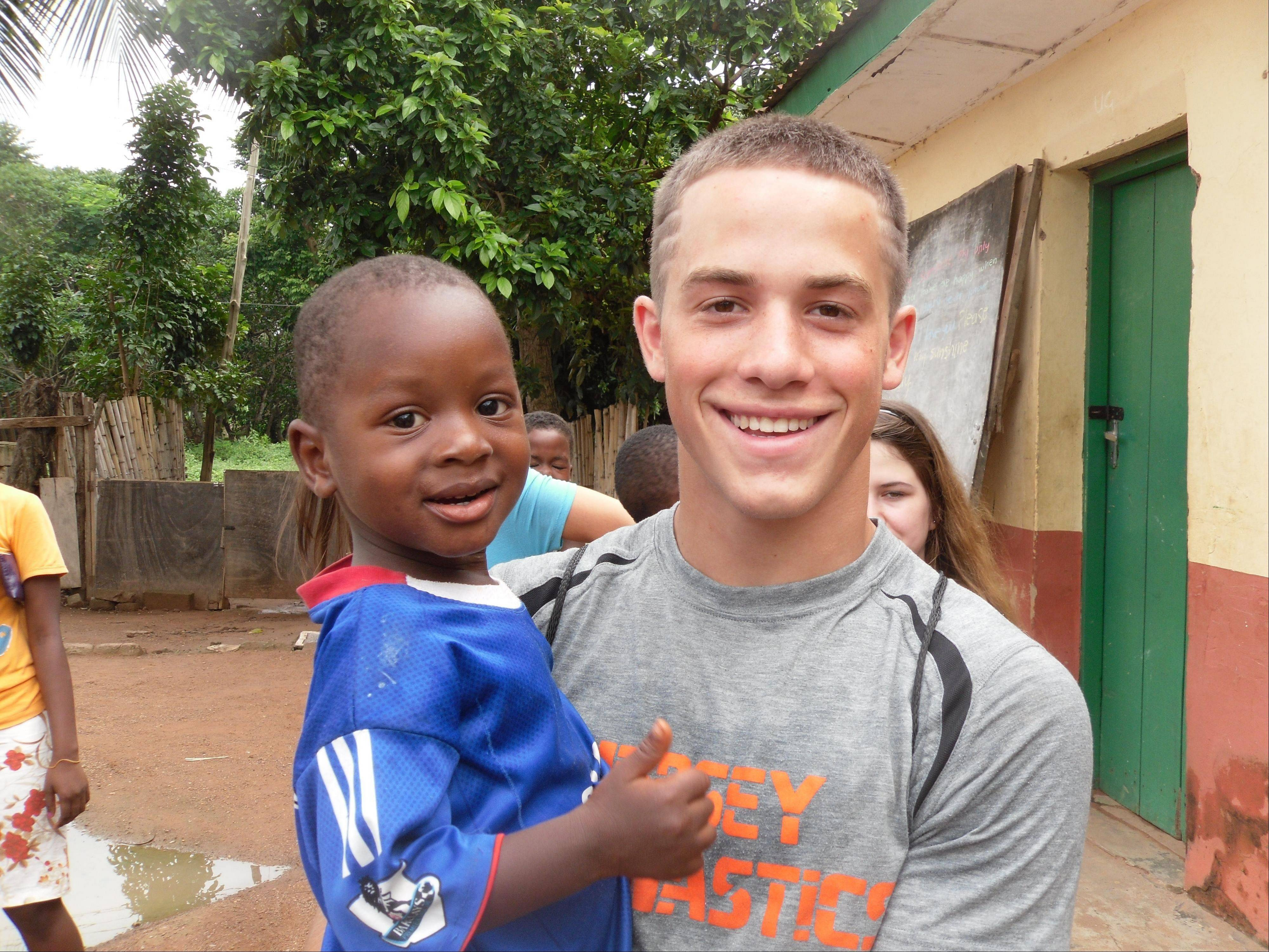 Hersey High School student Alex Baratta, 17, plays with one of the children from Ghana during his volunteer trip.