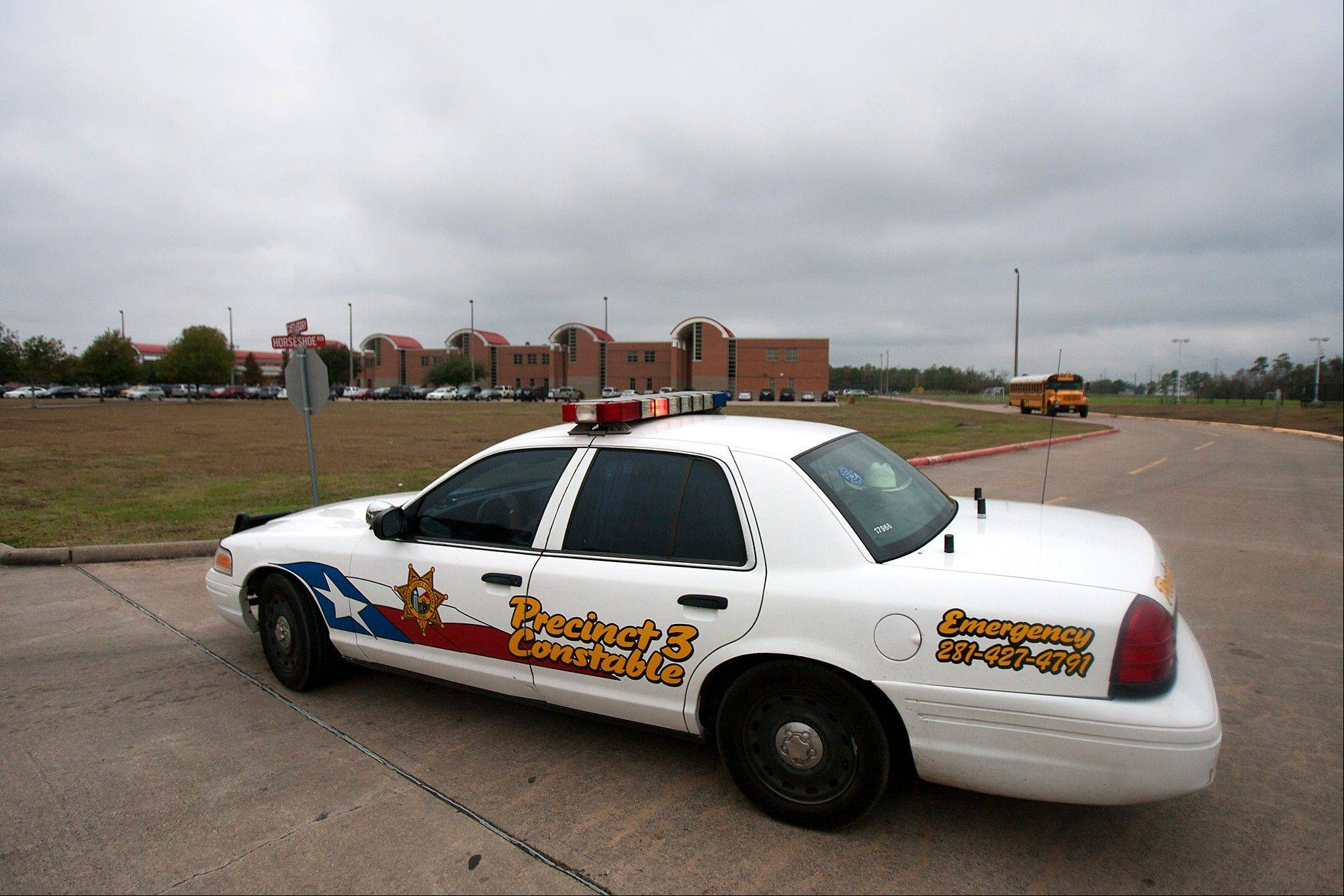 A police vehicle is parked near the entrance of North Shore High School after a shooting occurred Wednesday in Houston. Police say a high school student taken into custody after he sent a text message to a friend saying he wanted to hurt himself shot himself with a hidden gun while handcuffed inside a patrol car.