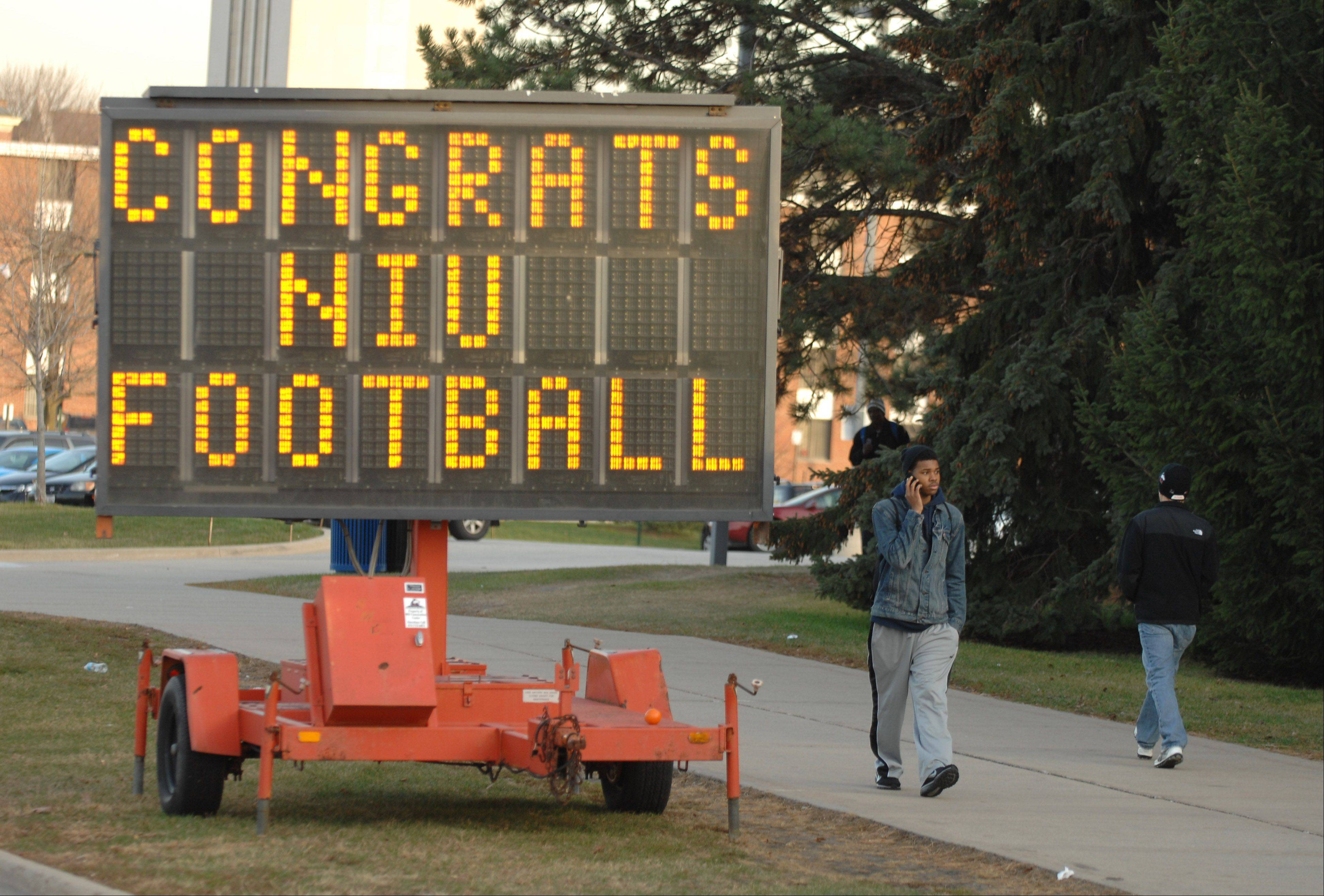 Pedestrians walk past a sign congratulating the football team for qualifying for the Orange Bowl. The sign is on Lucinda Avenue in DeKalb.