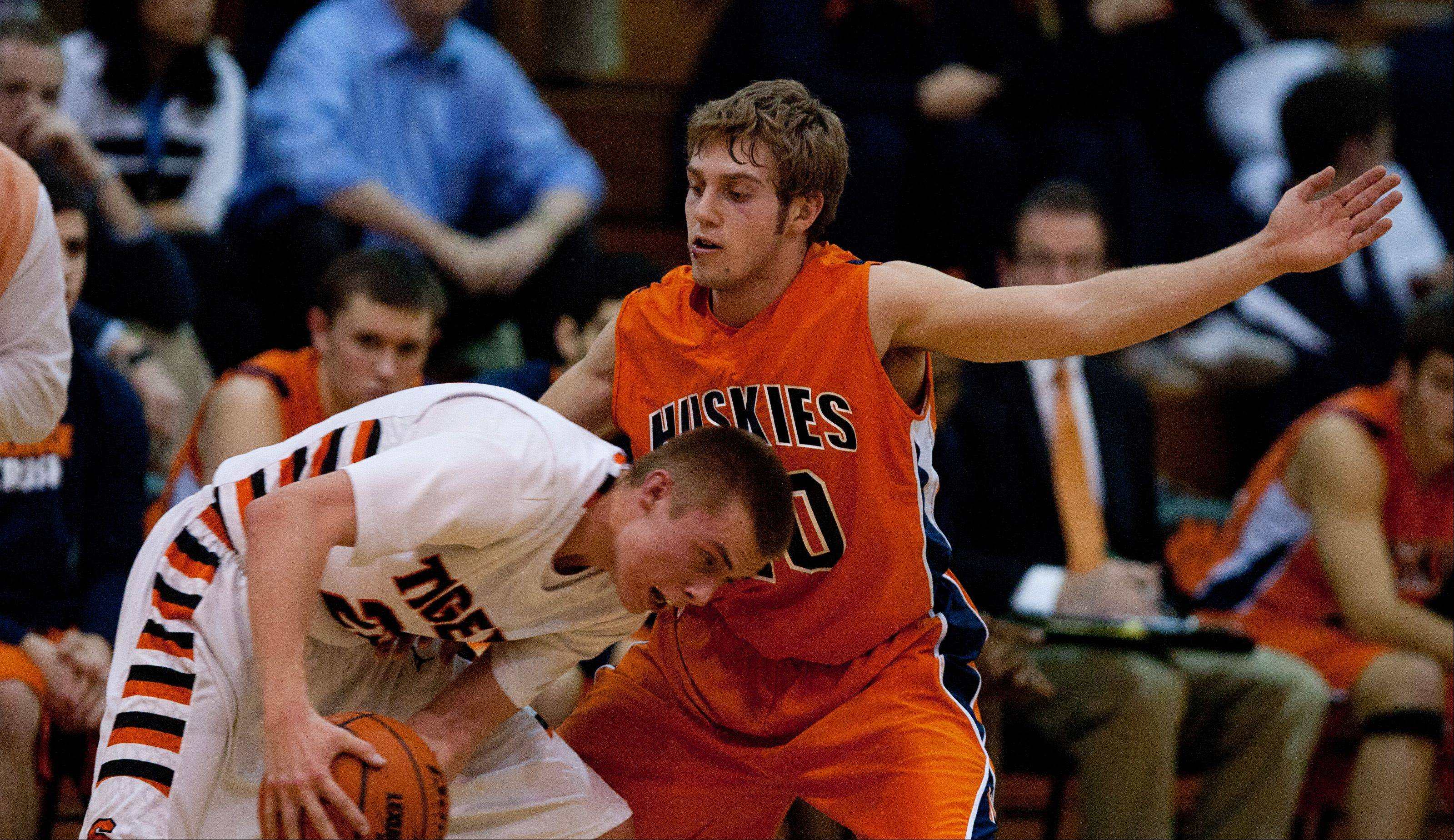Wheaton Warrenville South�s Michael Kramer, left, lowers his head against a Naperville North defender during boys basketball action in Wheaton.