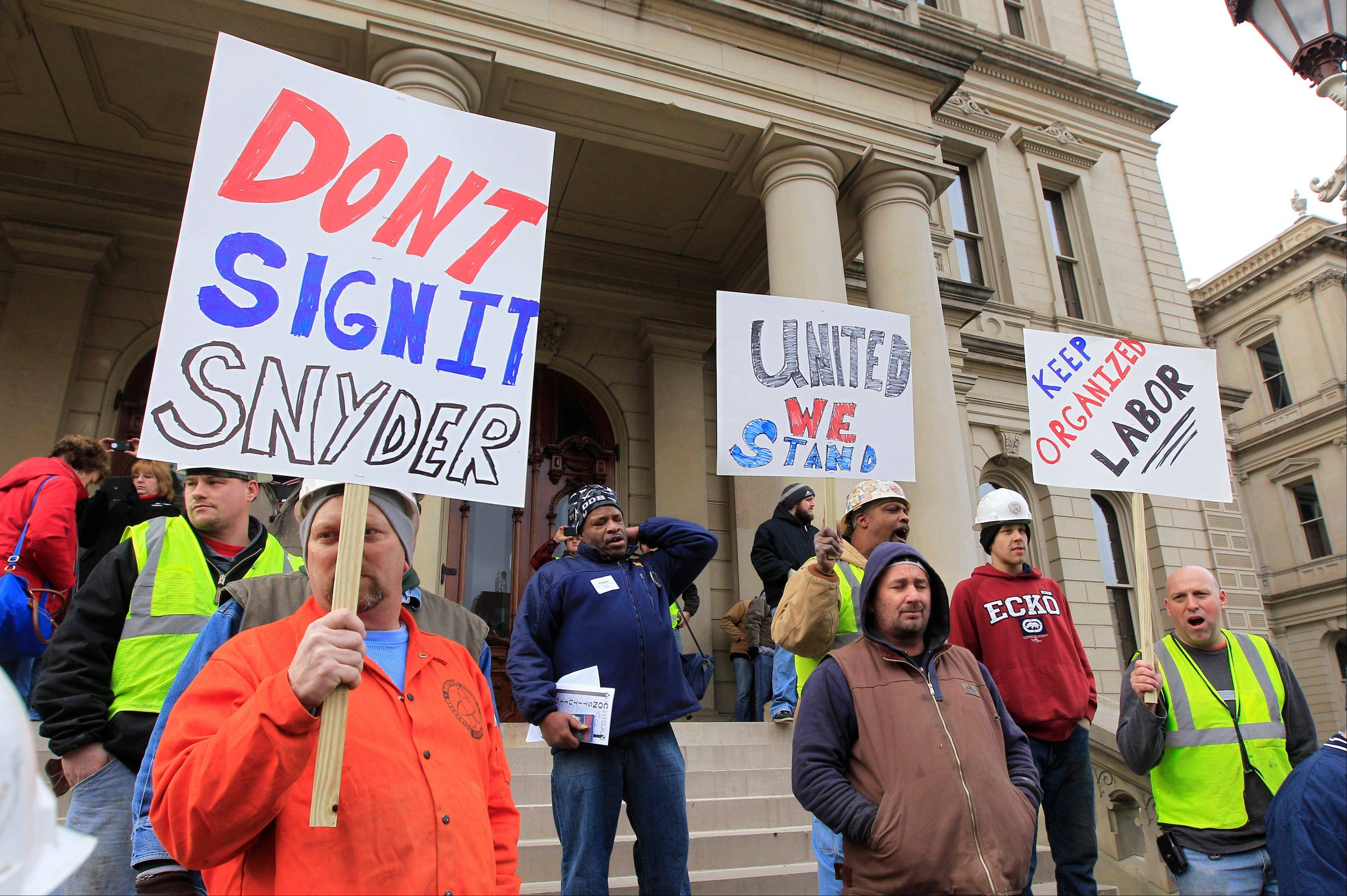 Union workers hold up a signs during a rally outside the Capitol in Lansing, Mich., Thursday, Dec. 6, 2012 as Senate Republicans introduced right-to-work legislation in the waning days of the legislative session.