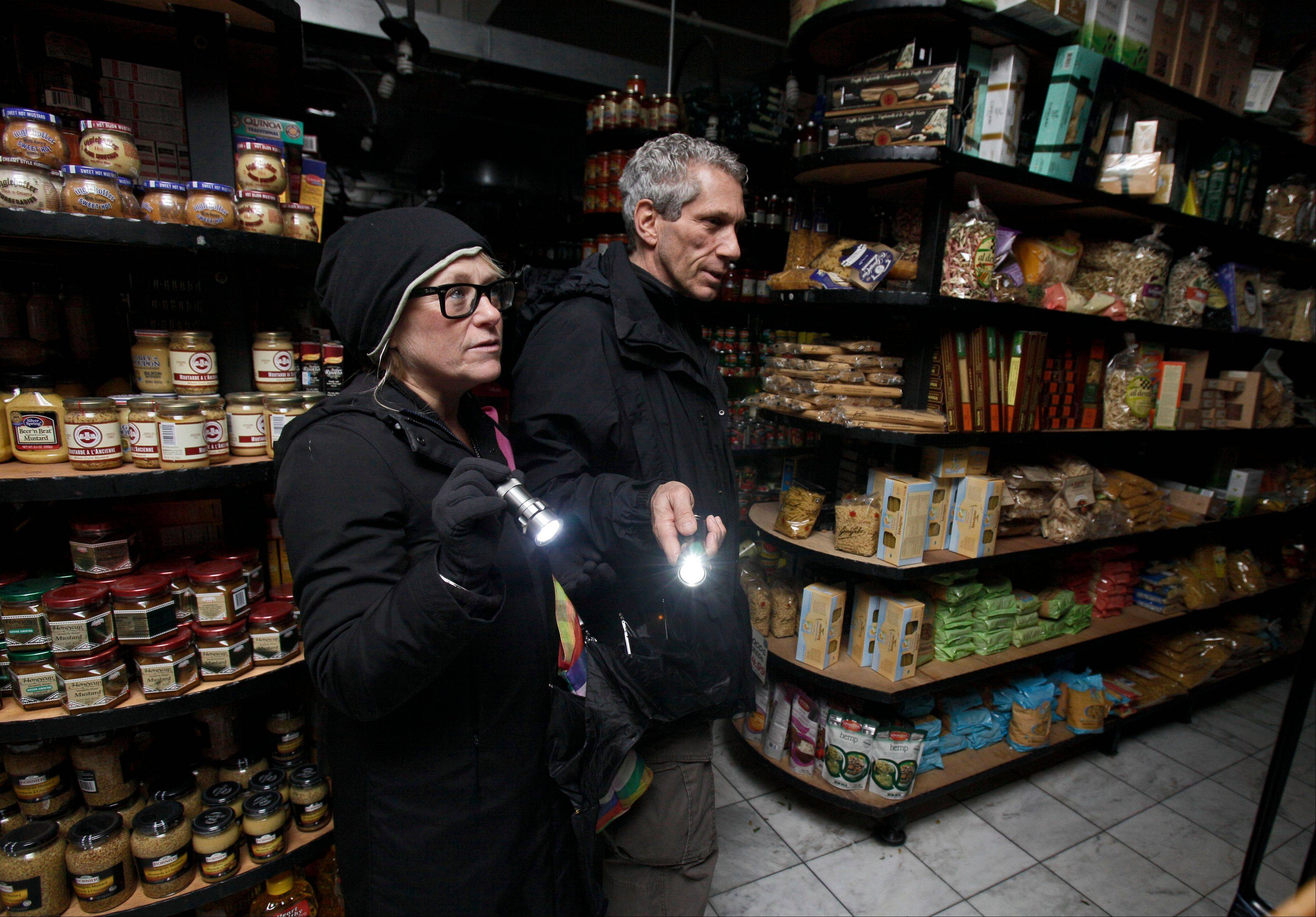 A couple shops for groceries by flashlight in the Tribeca neighborhood of New York, following a loss of power due to Superstorm Sandy in October. The government said Superstorm Sandy had only a minimal effect on the latest jobless figures.