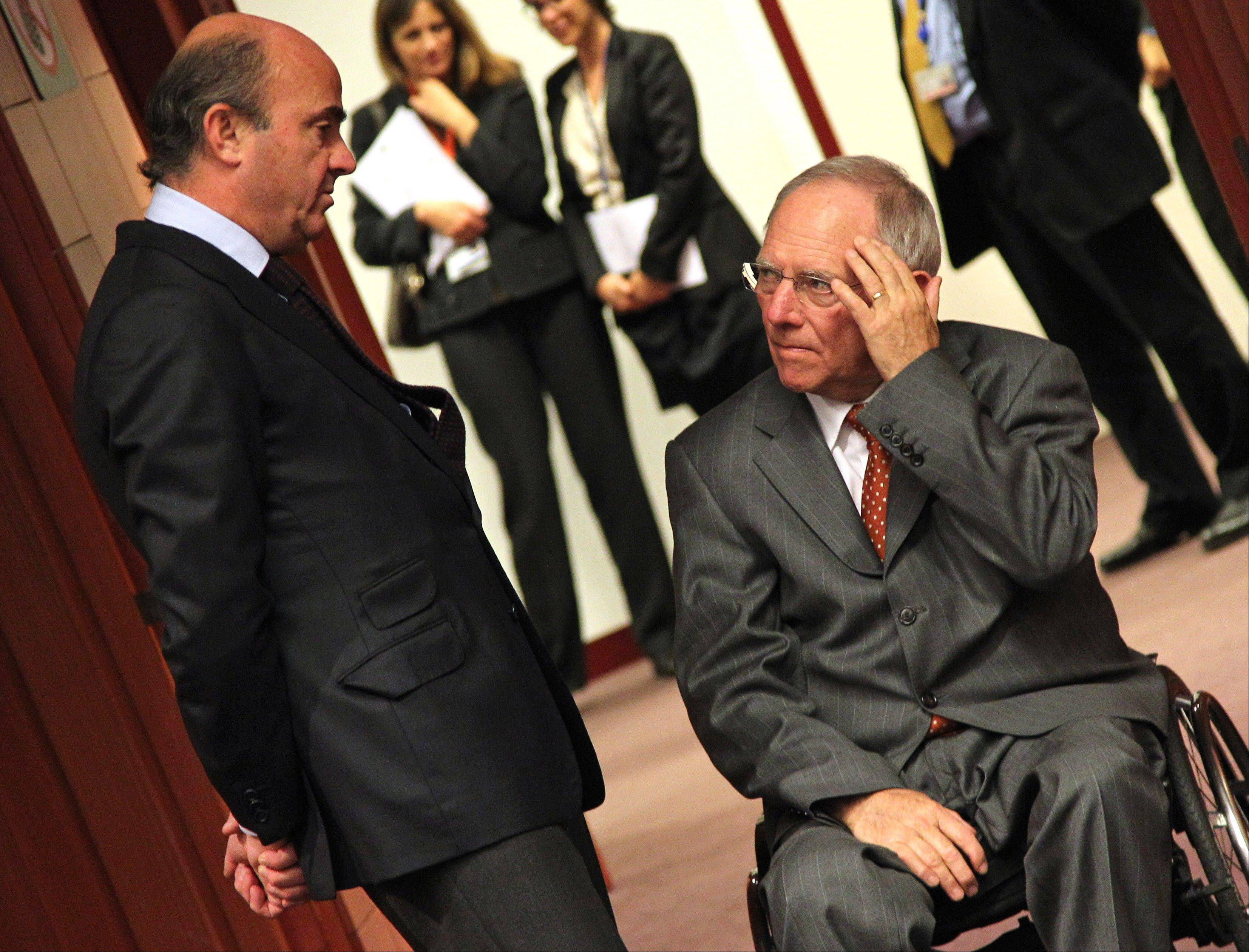 Spanish Economy Minister Luis de Guindos Jurado, left, talks with German Finance Minister Wolfgang Schaeuble, during the Eurogroup meeting, at the European Council building in Brussels, Monday.