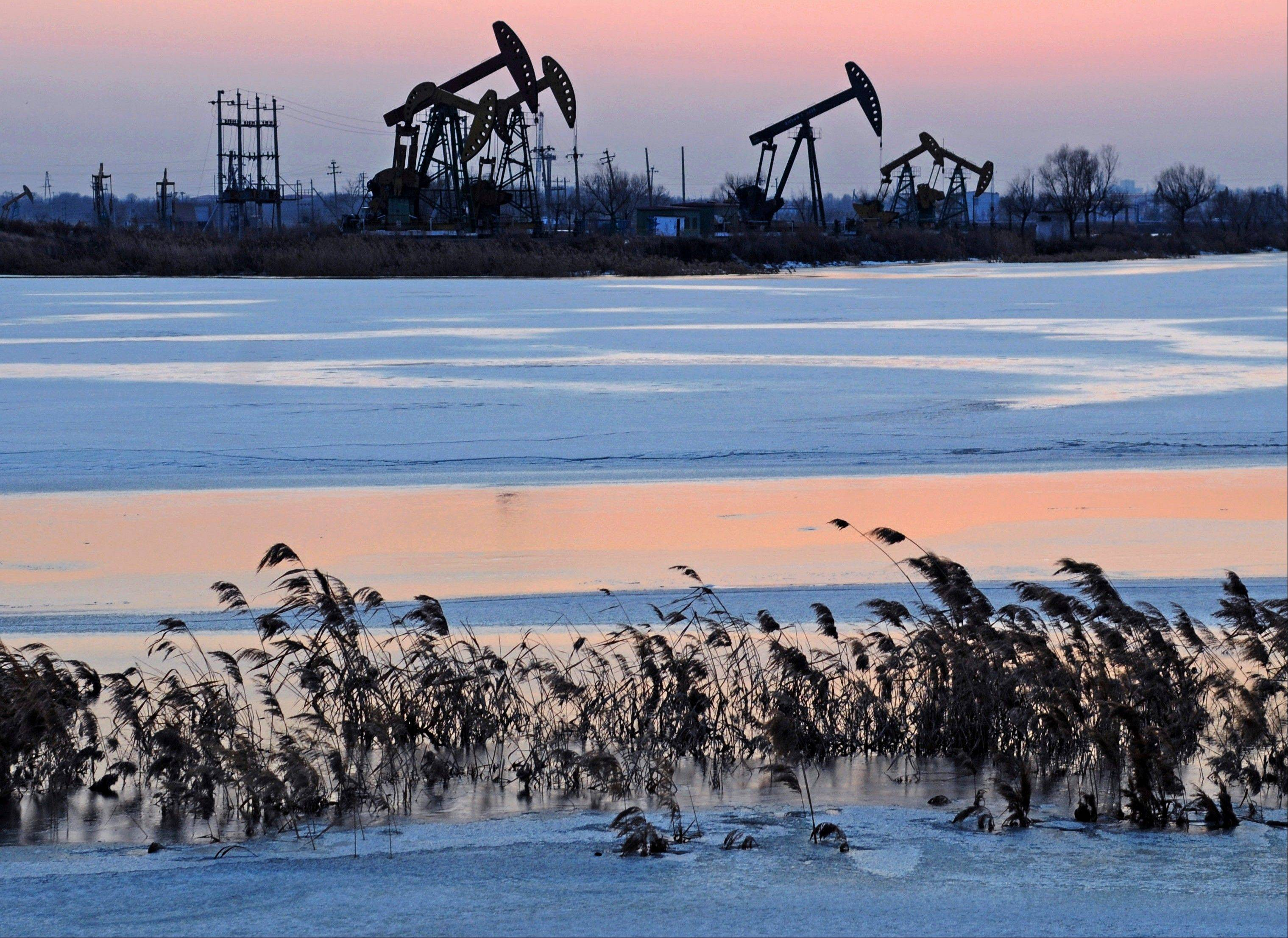 Oil rigs belonging to PetroChina are seen near the banks of a snow covered lake in Daqing in northeastern China's Heilongjiang province earlier this year.