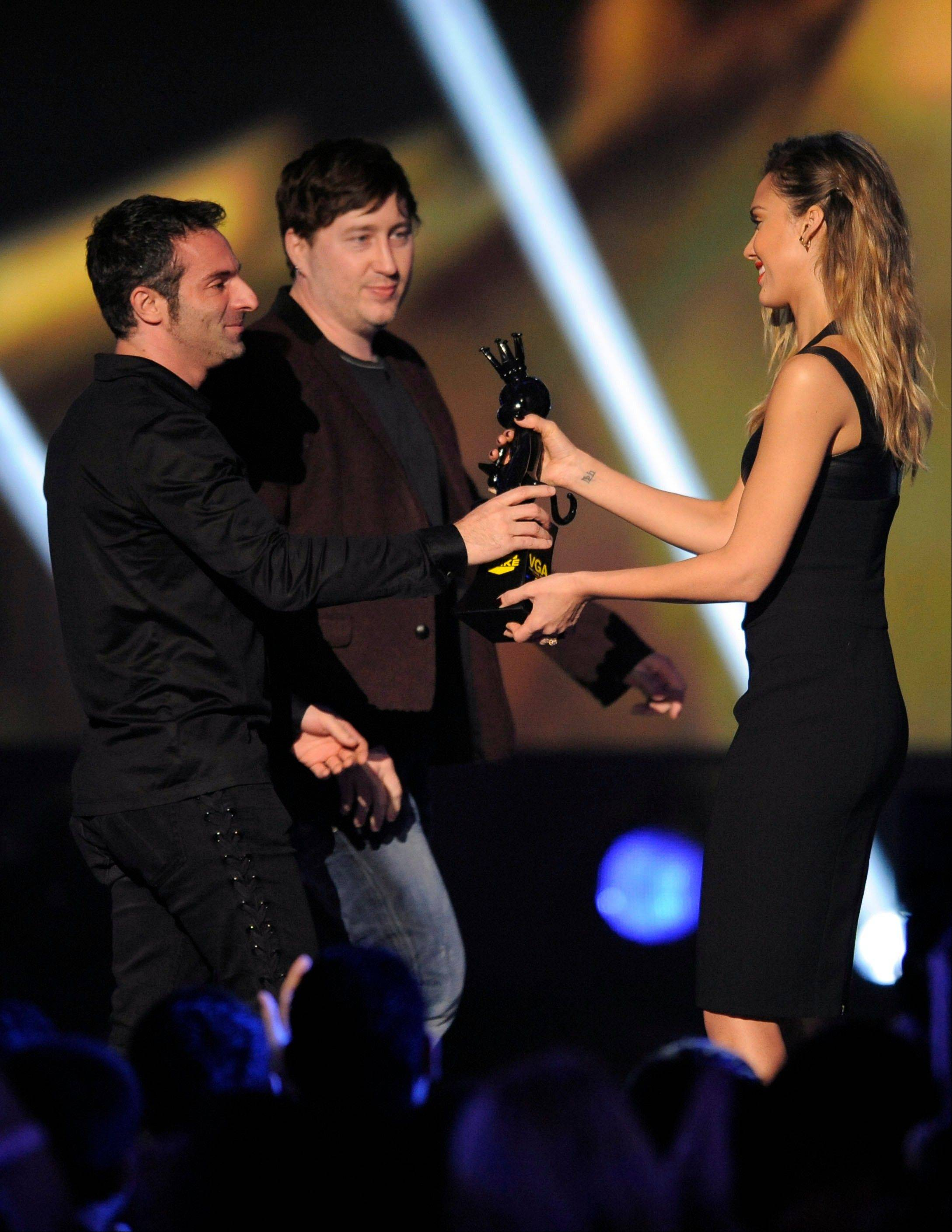 "From left, Jessica Alba presents the award for best action adventure to Raphael Colantonio and Harvey Smith for ""Dishonored"" Friday at Spike's 10th Annual Video Game Awards at Sony Studios."