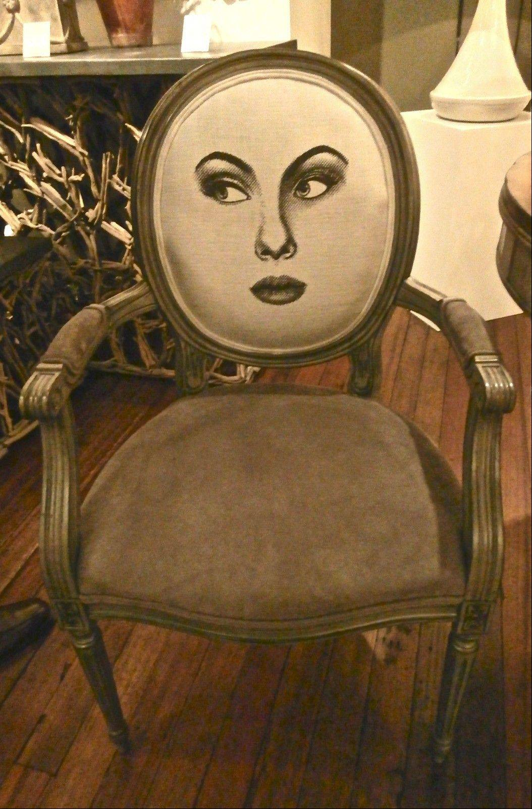 Currey & Company's Fornasetti-inspired fabric is upholstered on the front and back of the Palais armchair.