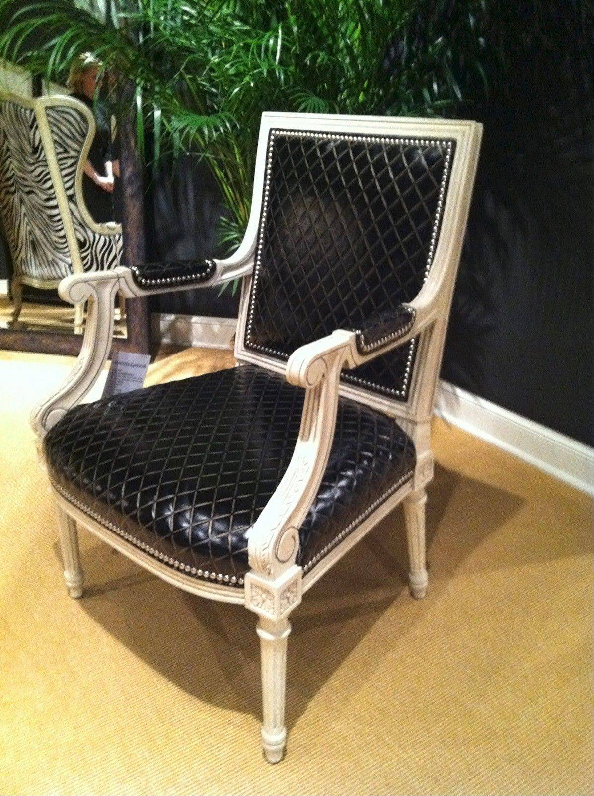 This Hancock & Moore Fowler chair upholstered in prism ebony leather with bisque trim finish and nickel nail heads feels like something Coco Chanel might have designed.