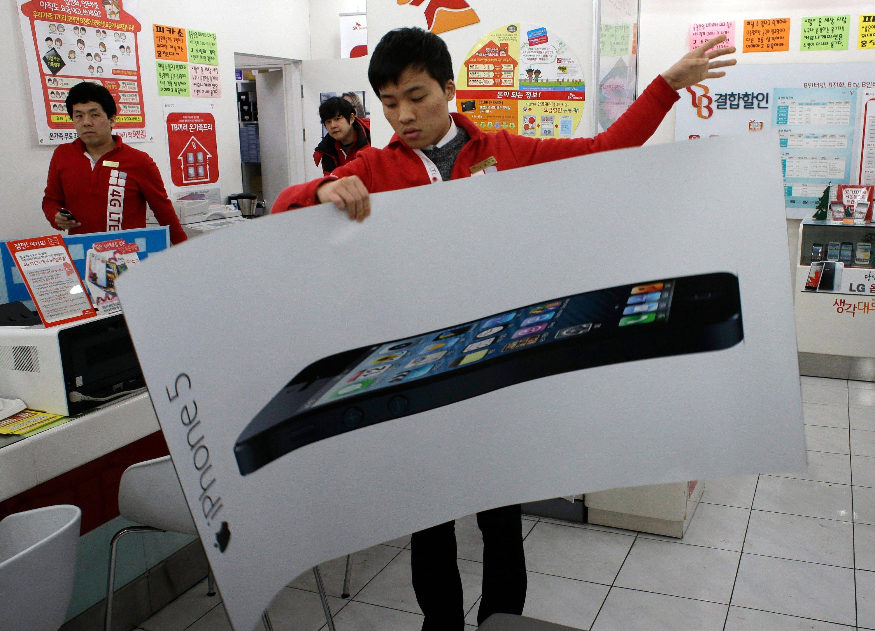 A clerk prepares to display a poster Friday of an Apple's iPhone 5 at a mobile phone shop in Seoul, South Korea.